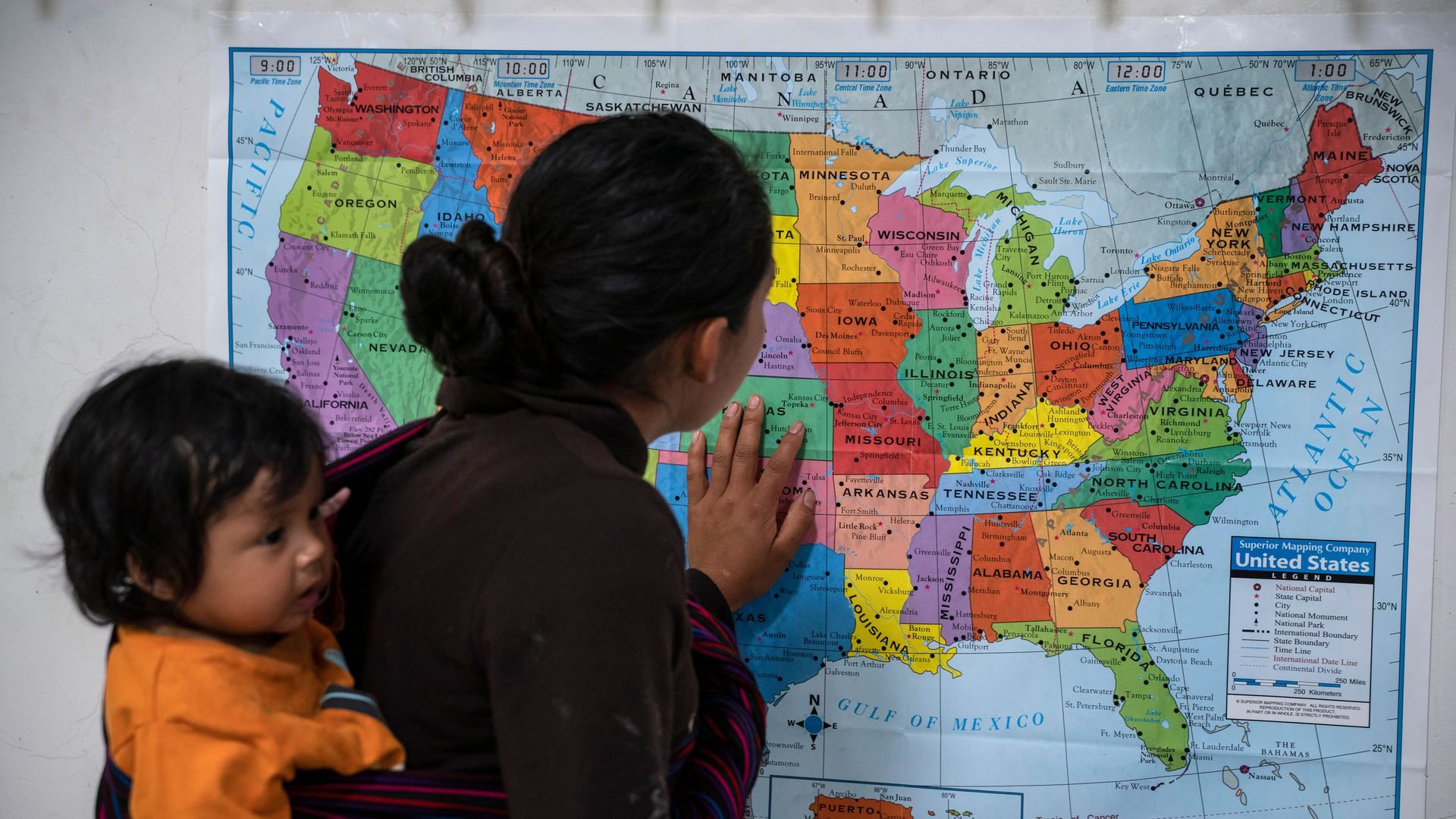 Guatemalan woman looking at a map of the U.S. with her baby