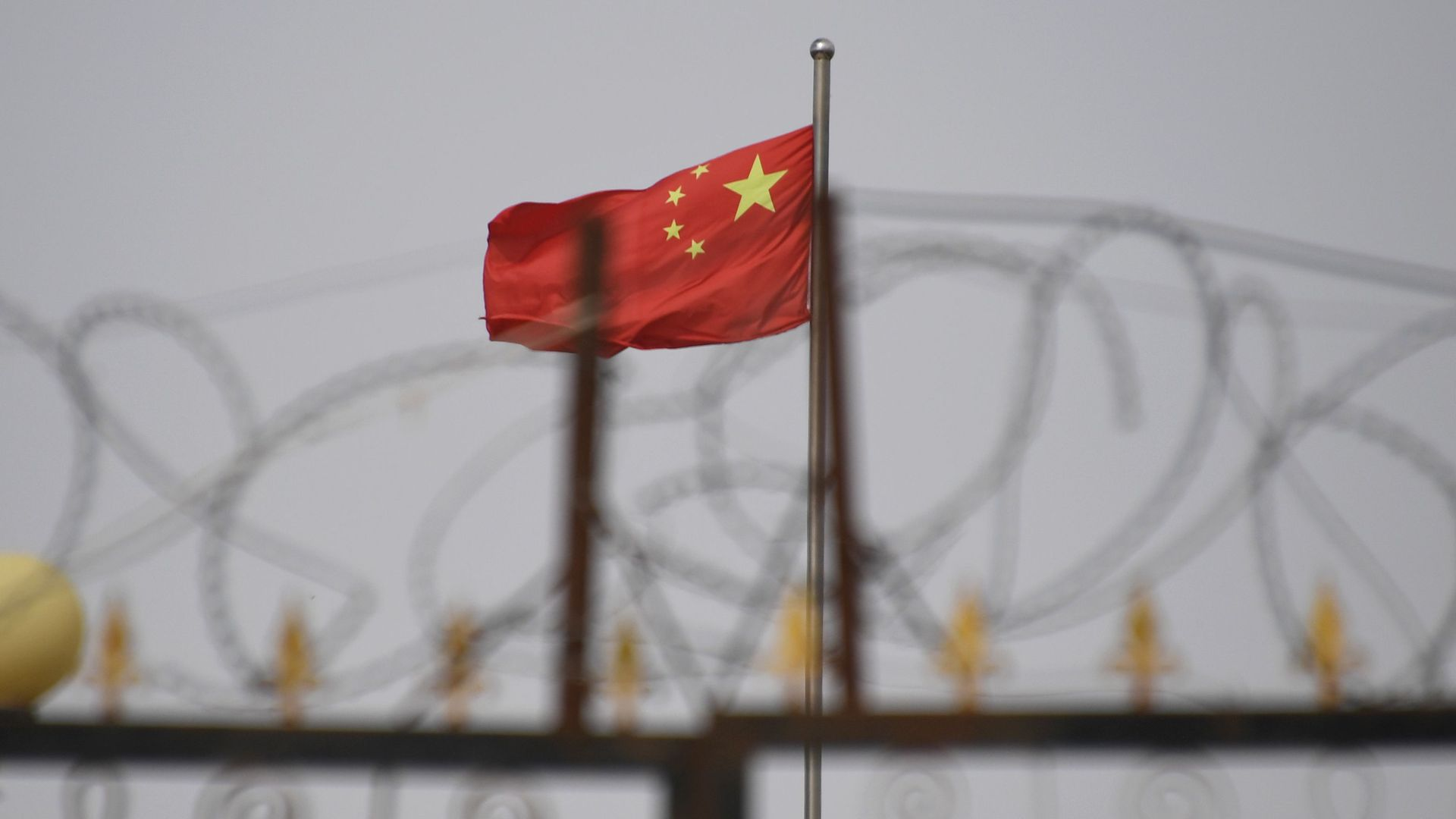 Chinese flag over barbed wire fence