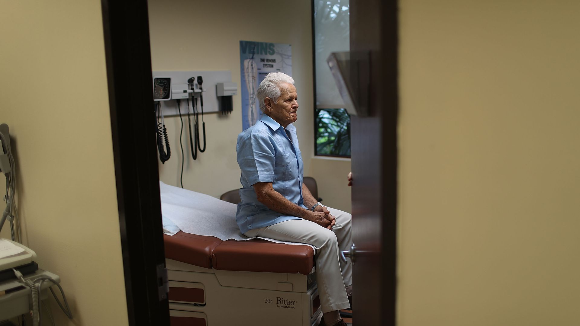 An elderly patients sits in a hospital exam room.