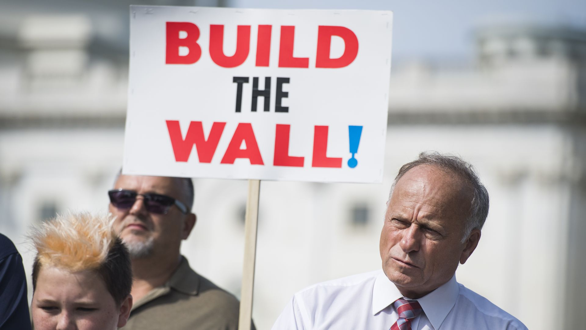 "Steve King with a supporter holding a ""Build the Wall"" sign"