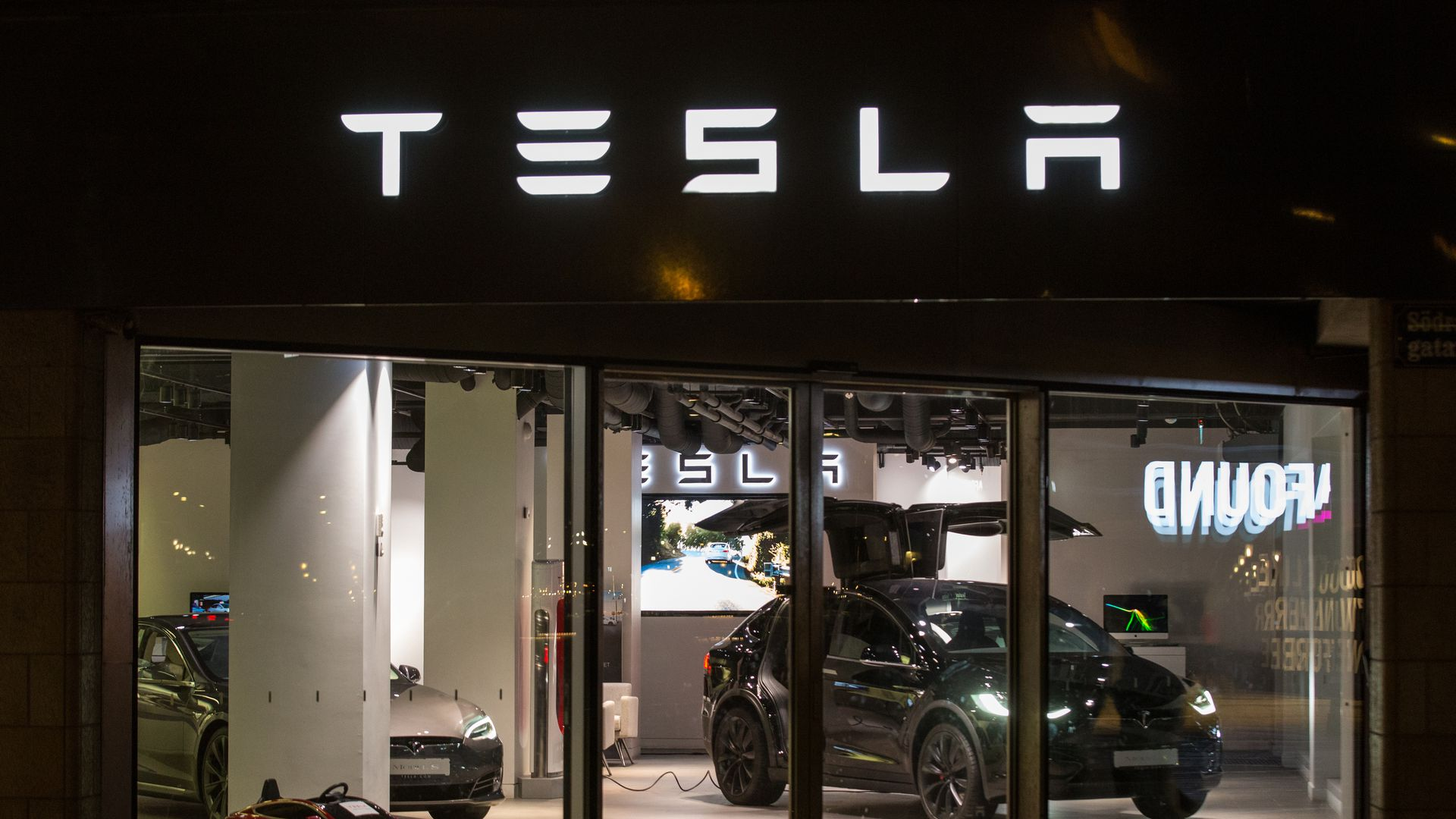 Photo of Tesla display at story lit up at nighttime