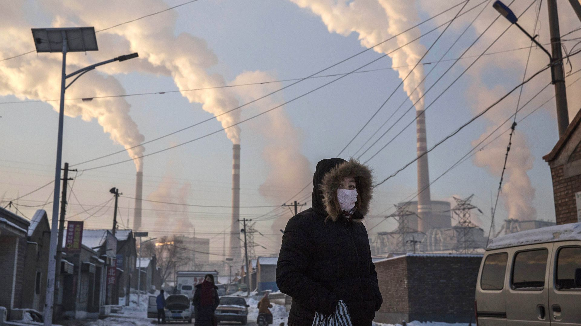 Smoke billows from stacks as a Chinese woman wears as mask while walking in a neighborhood next to a coal fired power plant on November 26, 2015 in Shanxi, China.