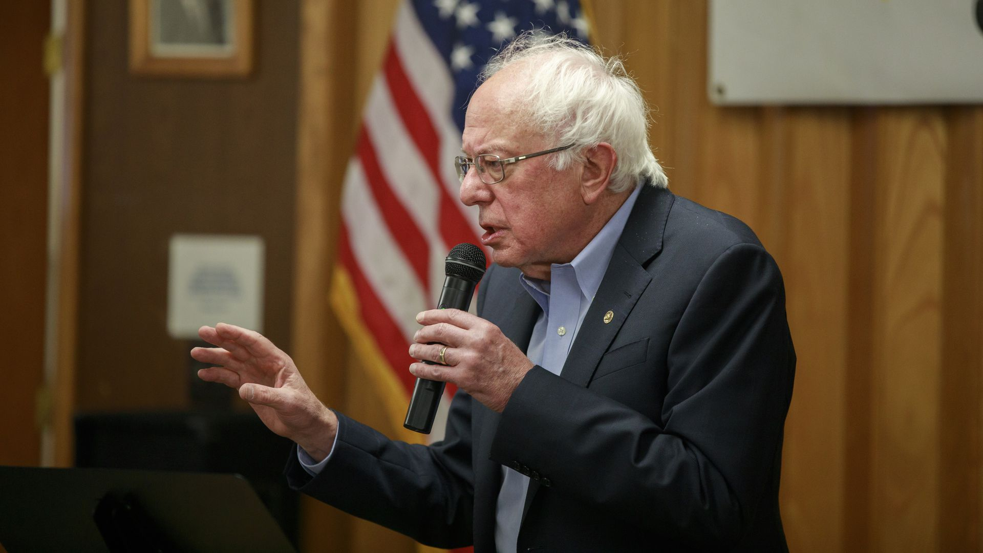In this image, Bernie Sanders speaks into a microphone with an American flag behind him.