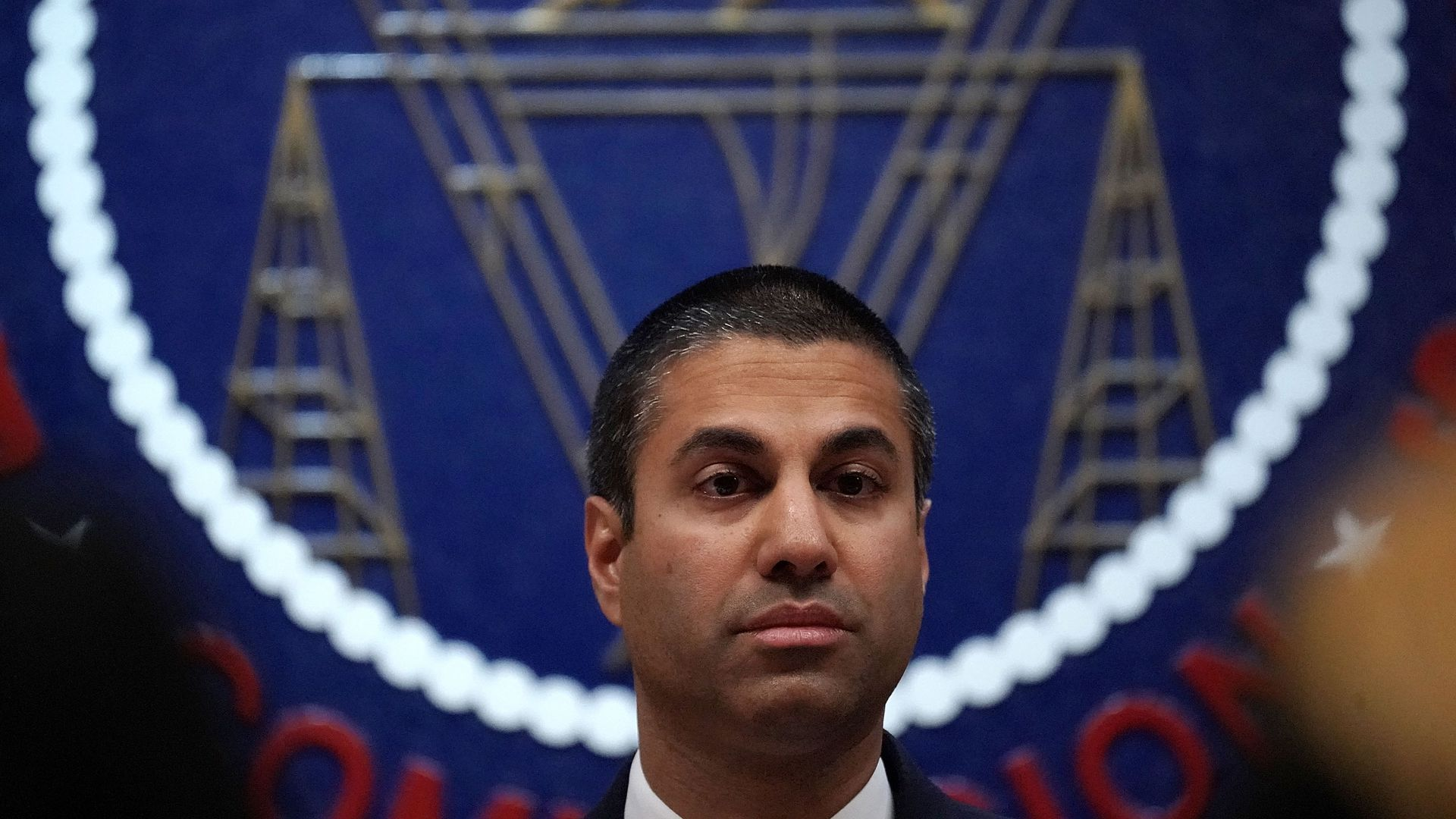 FCC Chairman Ajit Pai sits in front of the seal of the agency
