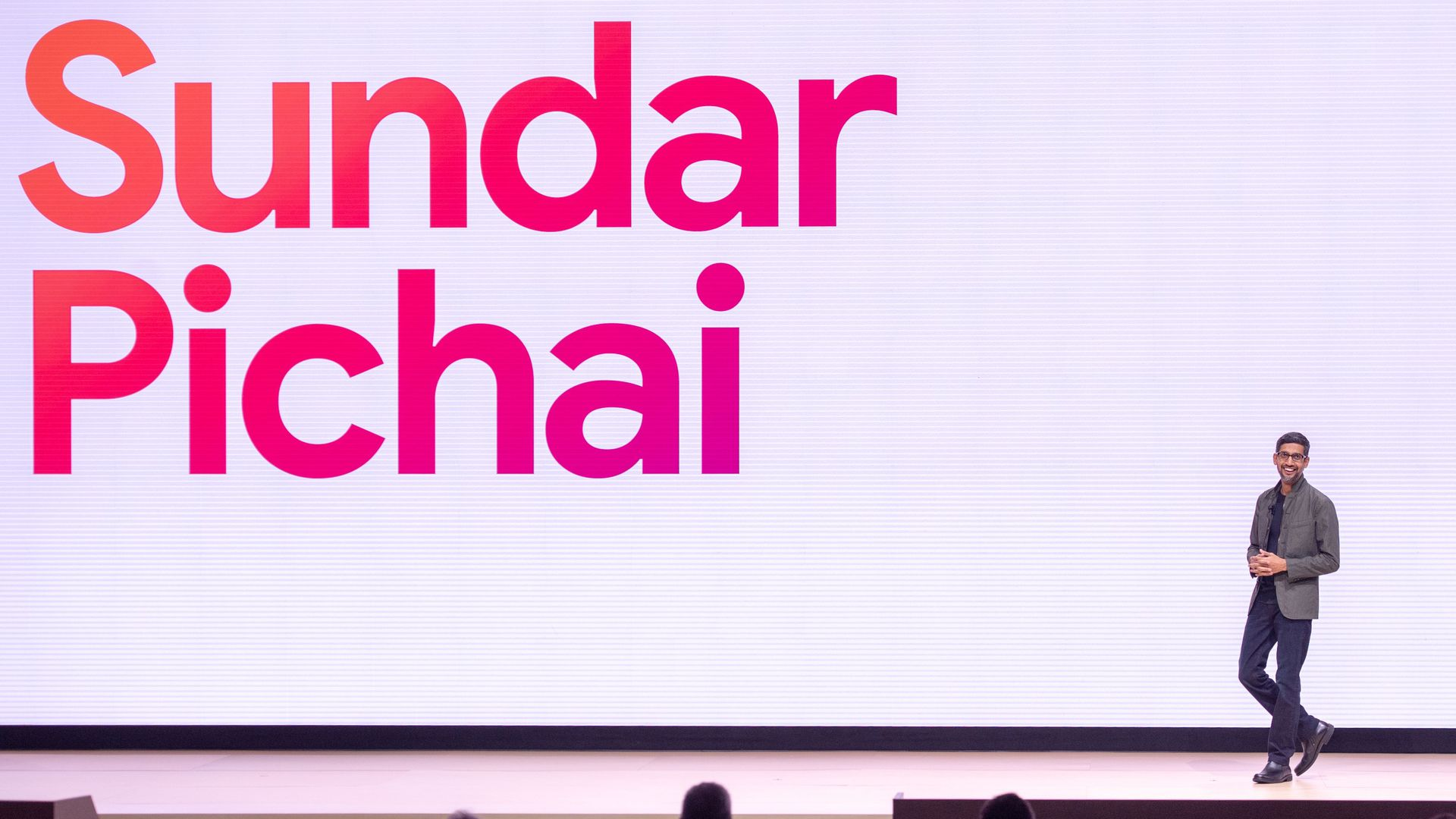 Sundar Pichai walks on a stage where a screen displays his name.