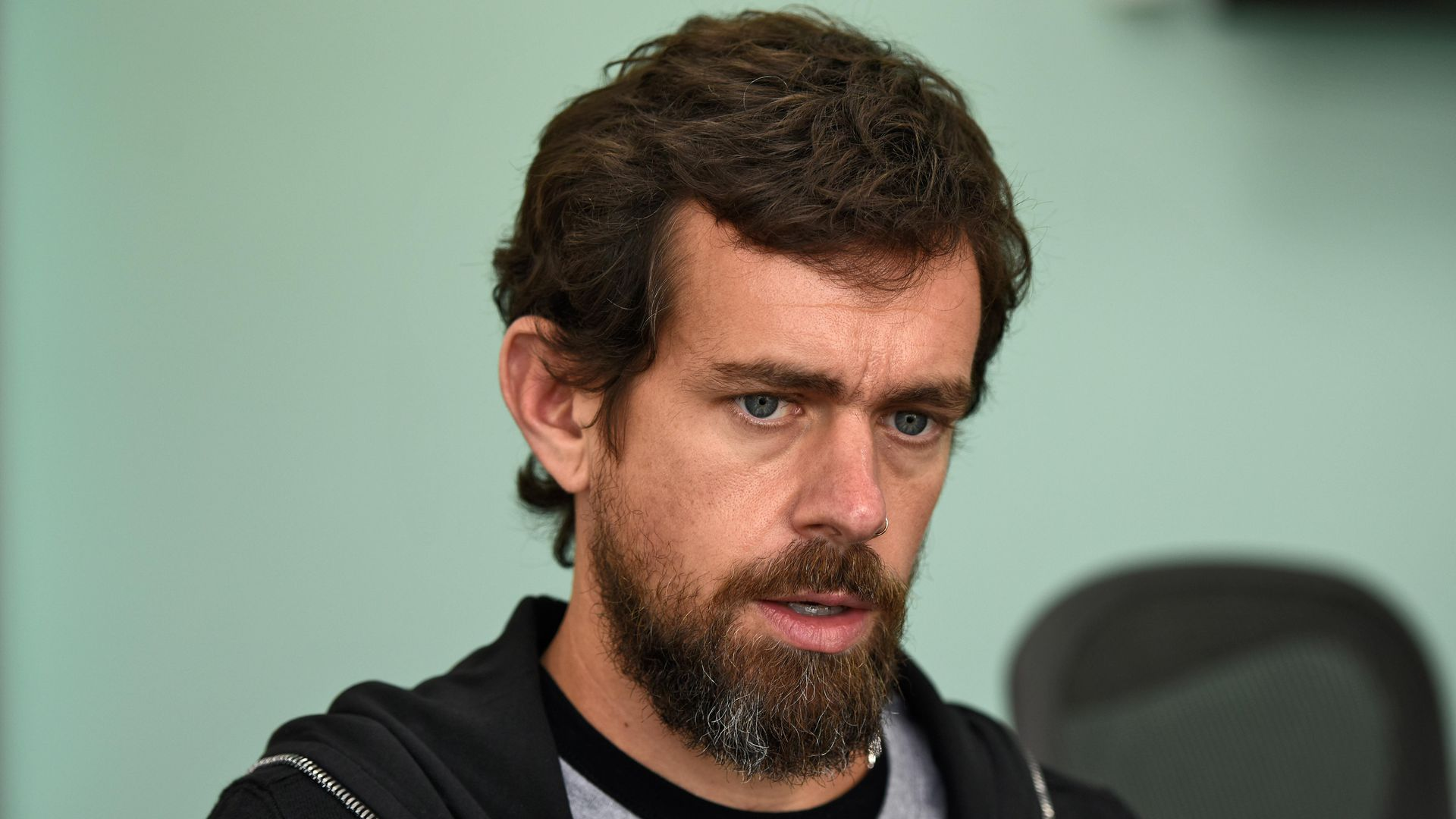 In this image, Dorsey is speaking while wearing a shirt and a hoodie.