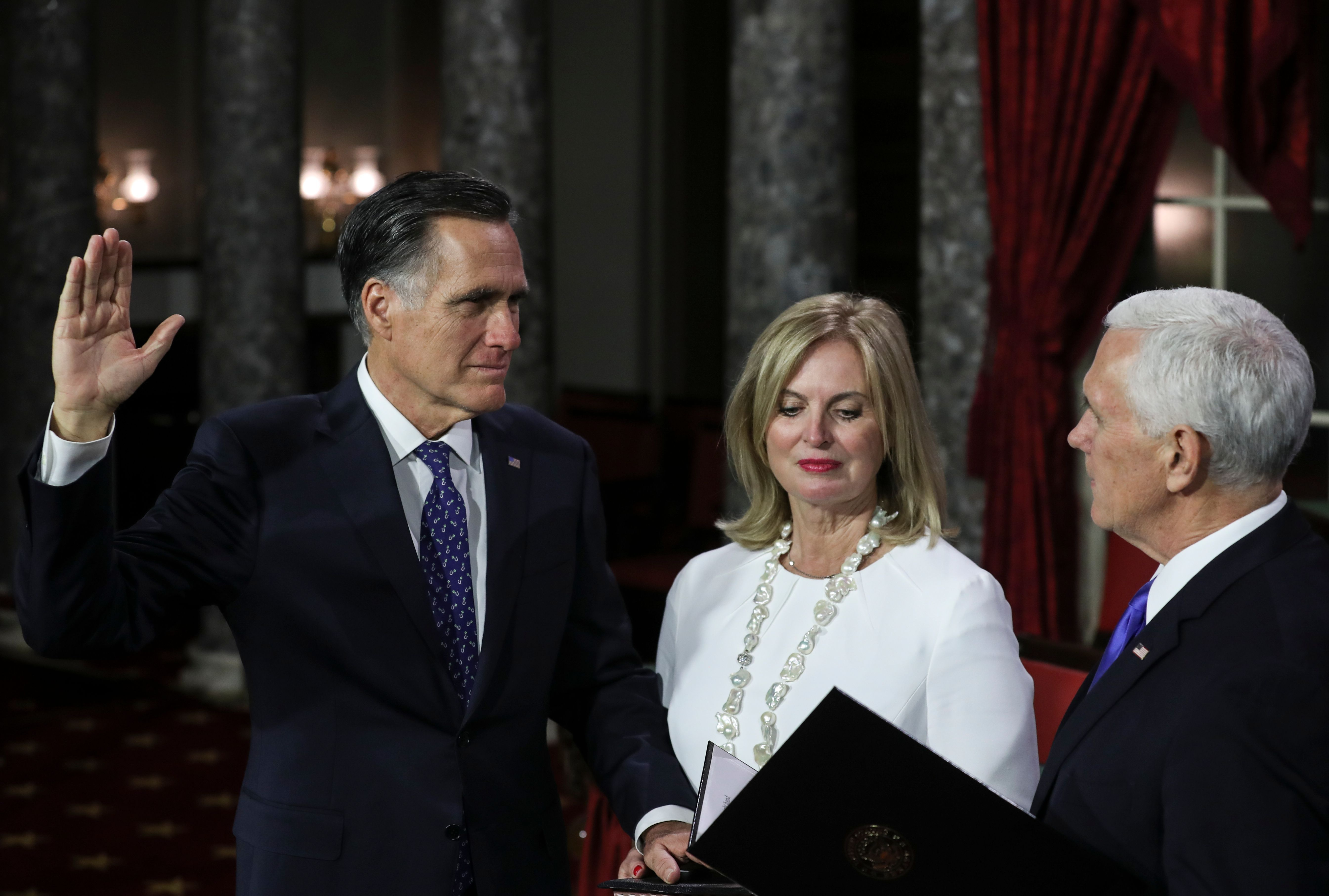 Mitt Romney being sworn in, next to his wife and Mike Pence.
