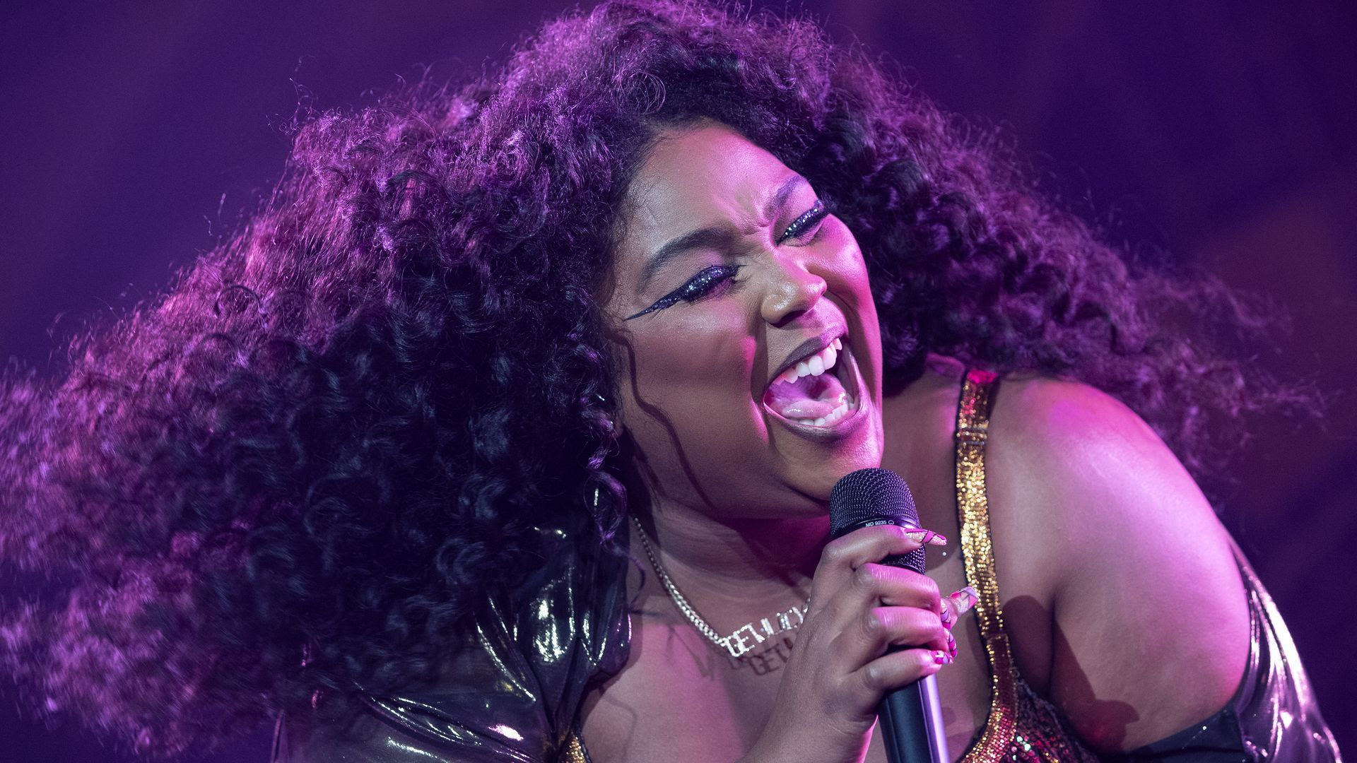 Lizzo sings into a microphone with purple light shining on her face.