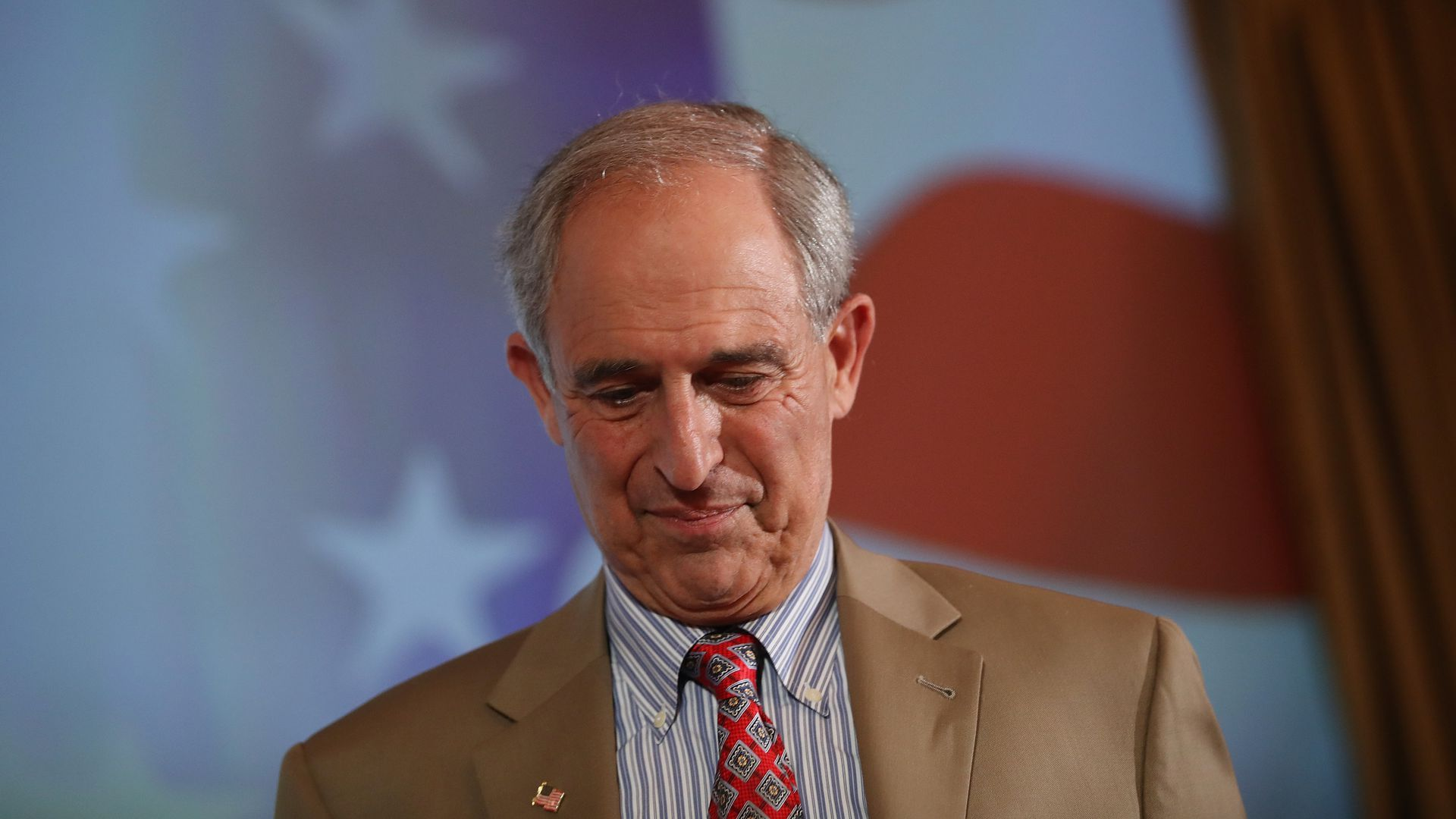 Lanny Davis looks down while on stage