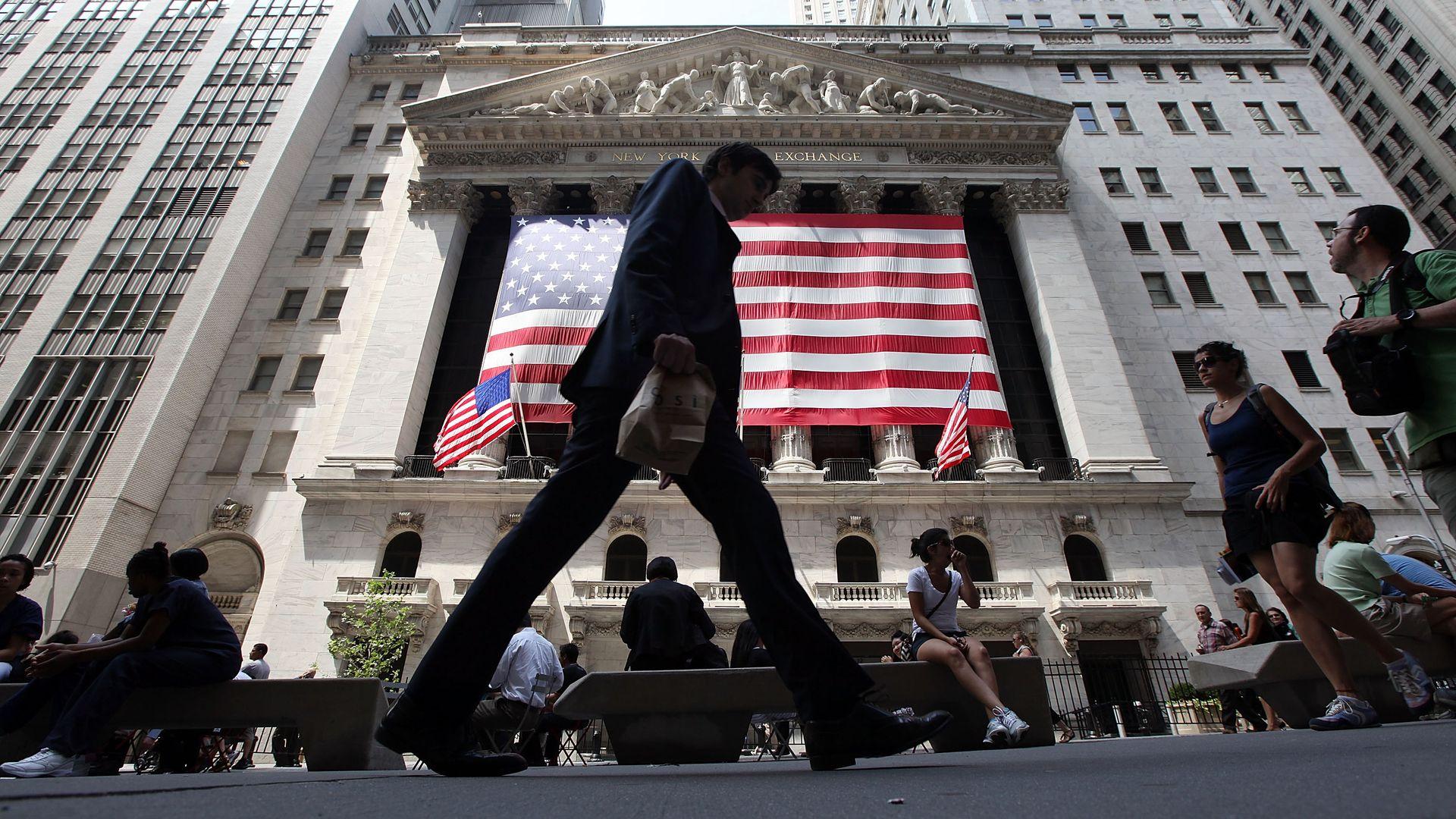 People walk past the New York Stock Exchange.