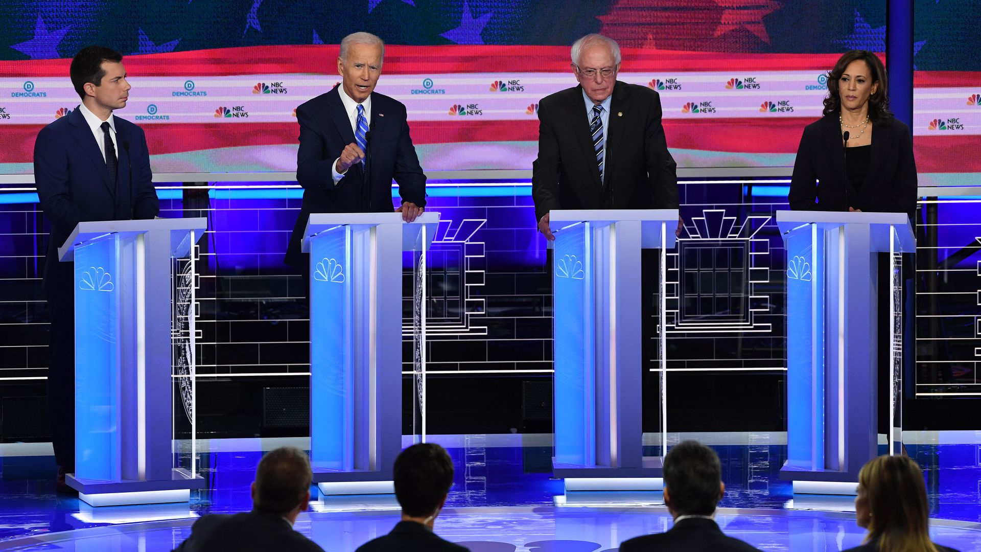 In this image, Buttigieg, Biden, Bernie and Harris stand at separate podiums on the debate stage.
