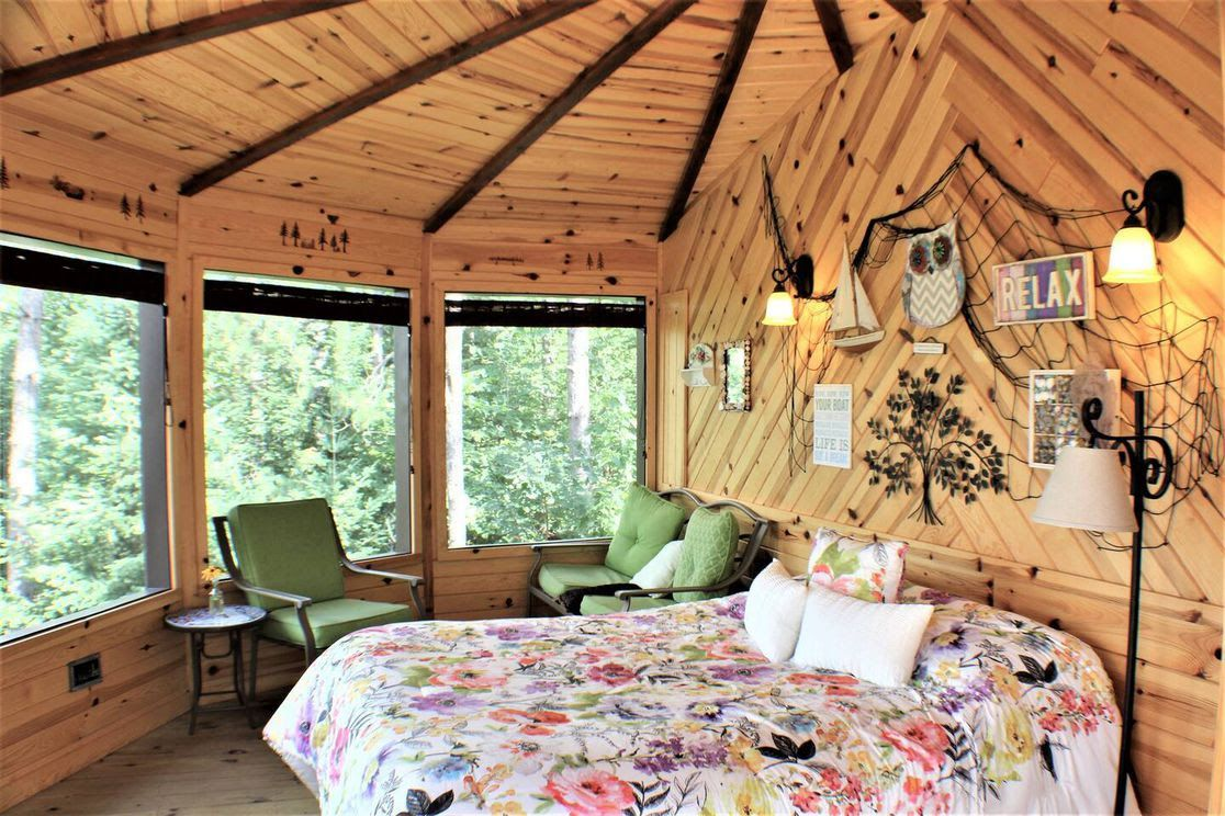 The interior of a Minnesota treehouse cabin with a bed and three chairs.