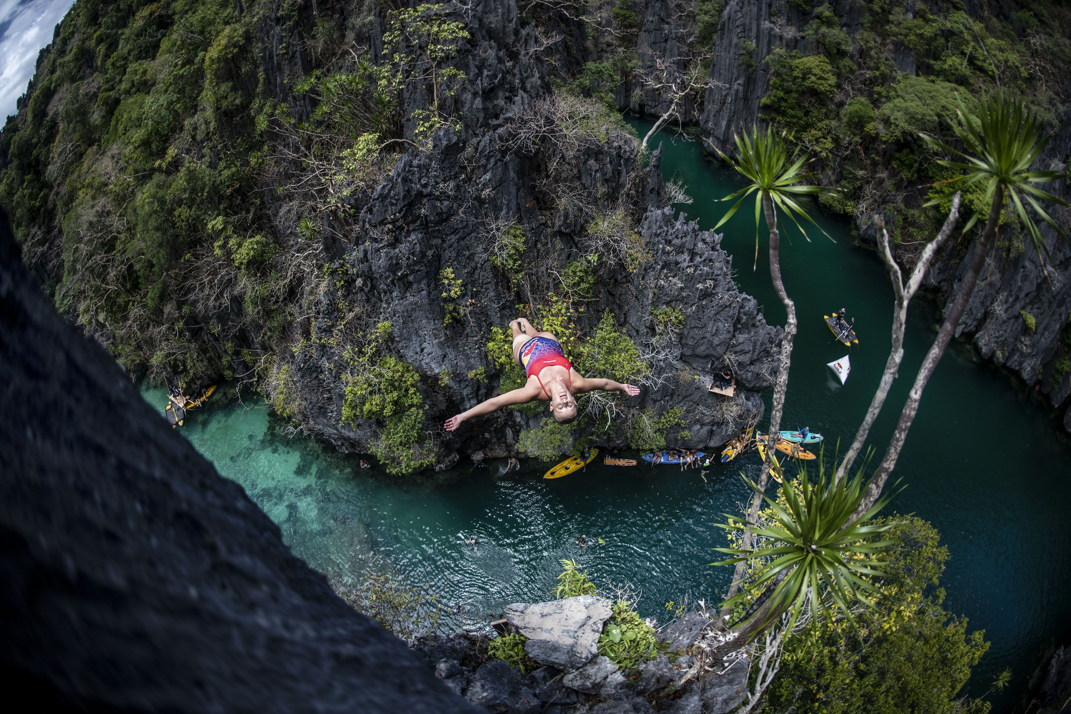 Woman diving off a cliff backwards