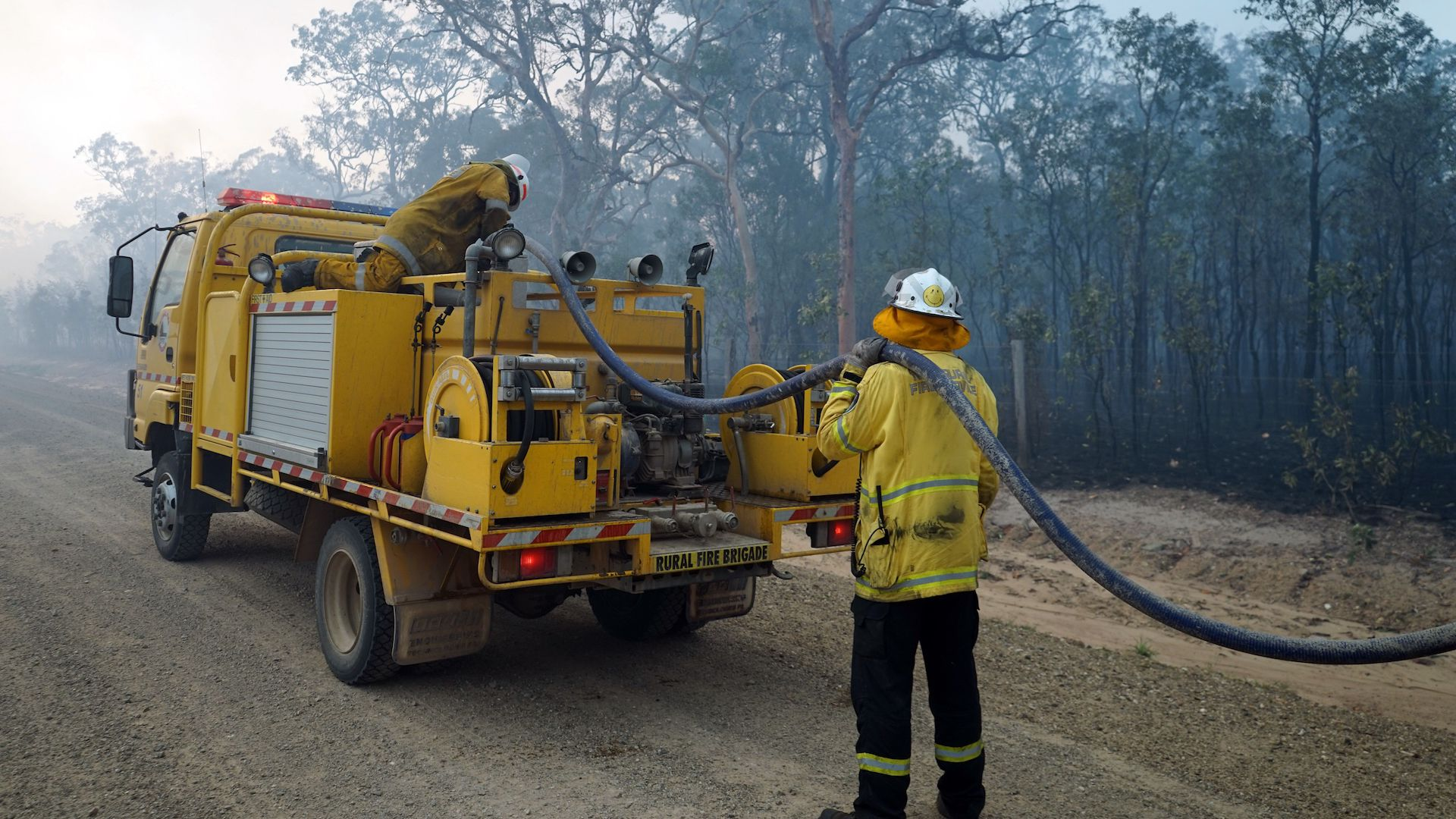 Firefighters refill their water from a water tanker in Pacific Drive in Deepwater National Park area of Queensland on November 28, 2018.