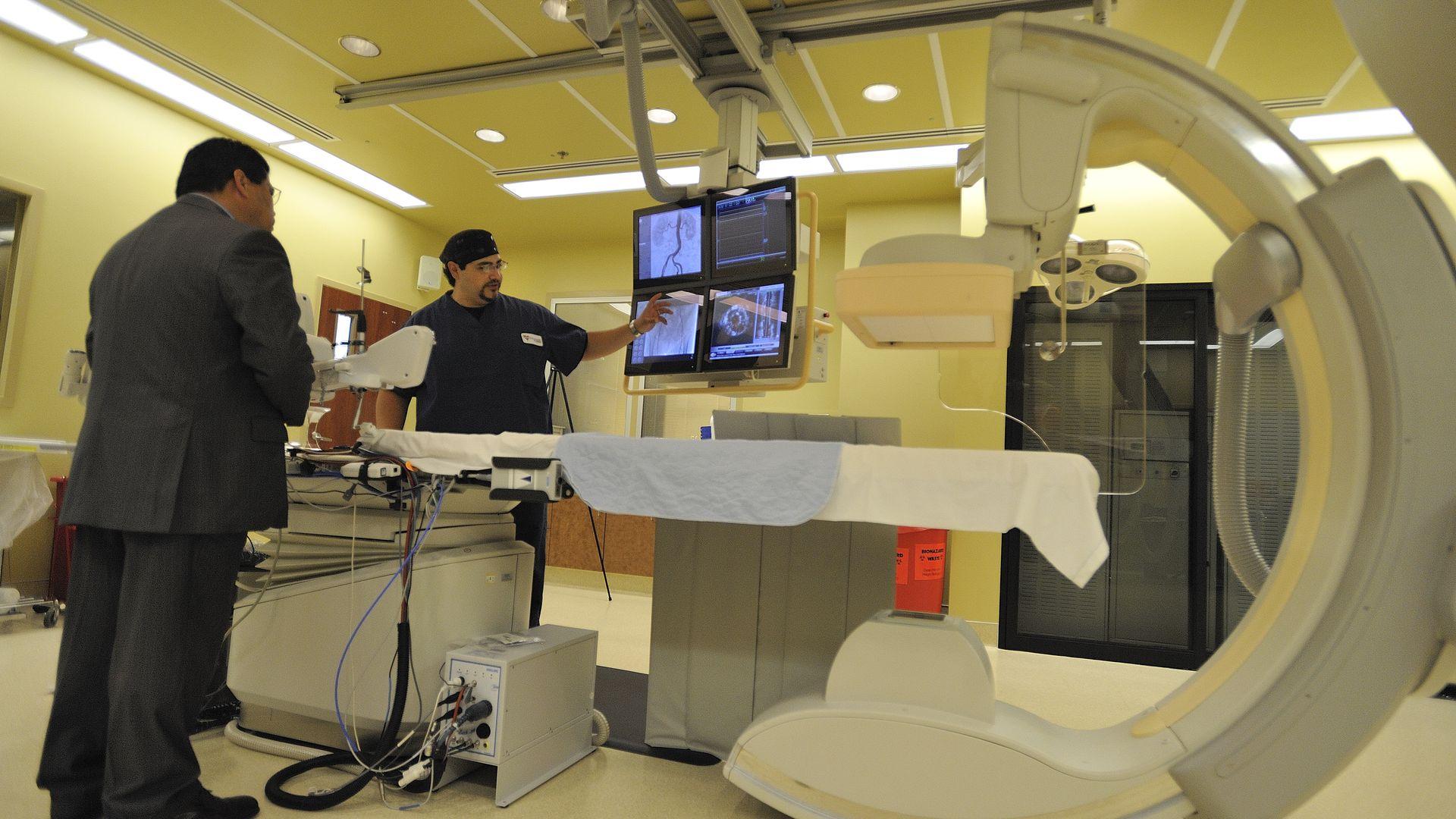 A health care technician points to computer screens near a cardiac cath machine.