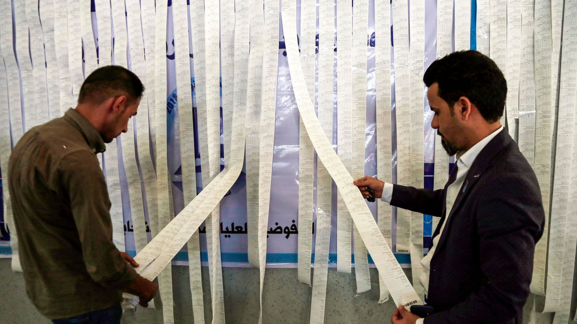 Iraqi electoral commission employees examine electronic counting machine print-outs in the central holy city of Najaf on May 13, 2018.