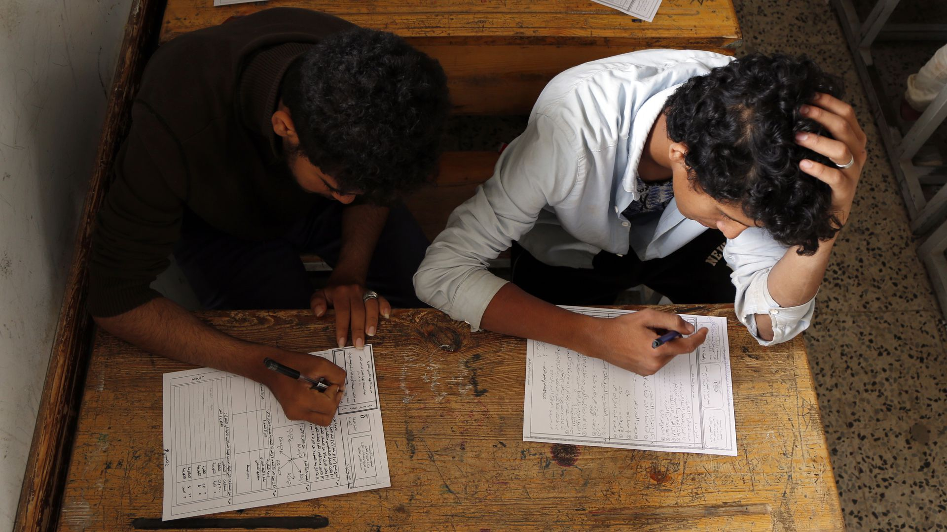 In this image, two male students sit at a desk while taking a test on separate sheets of paper.