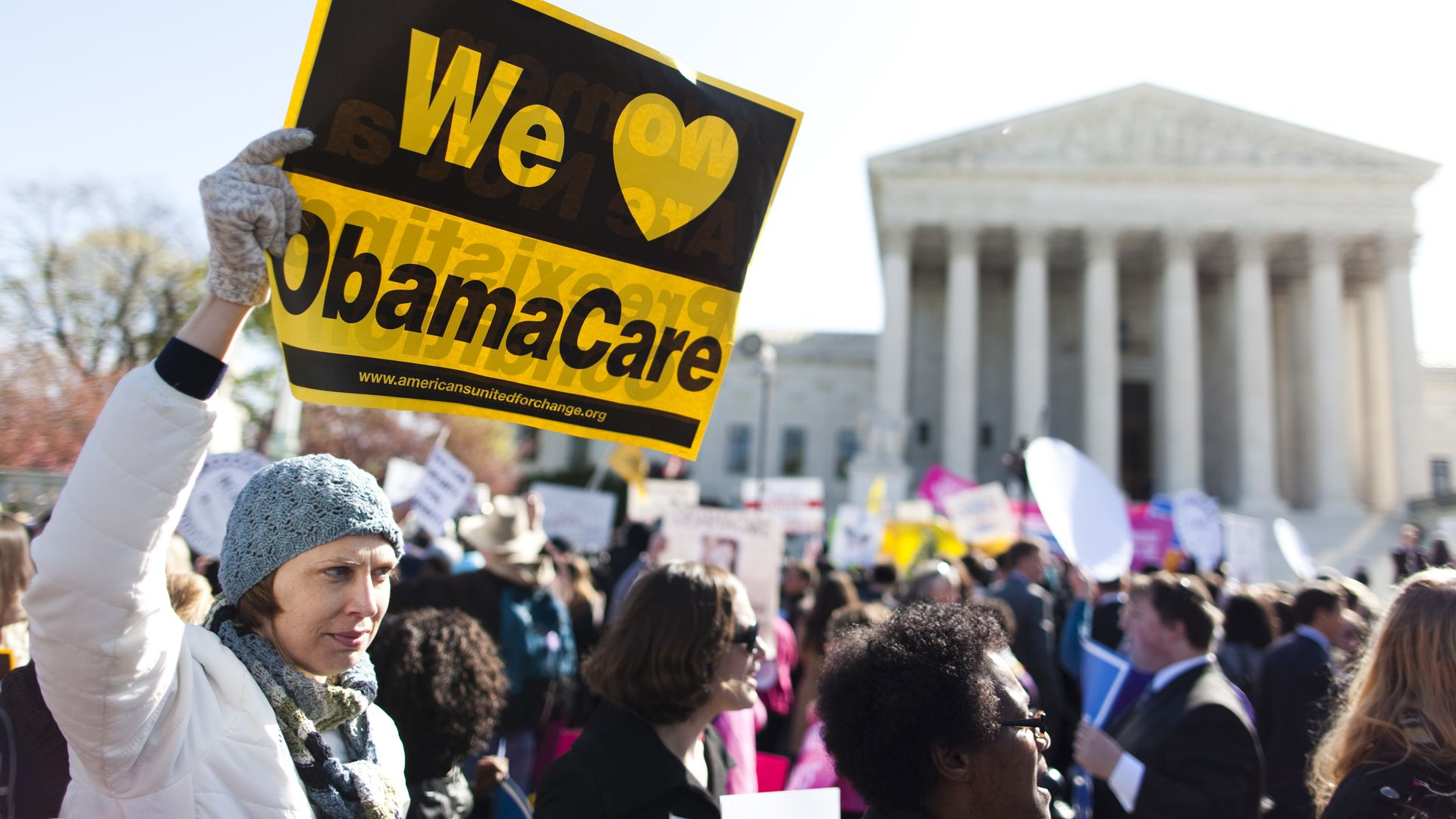 A protestor waving a pro-ACA sign outside the Supreme Court