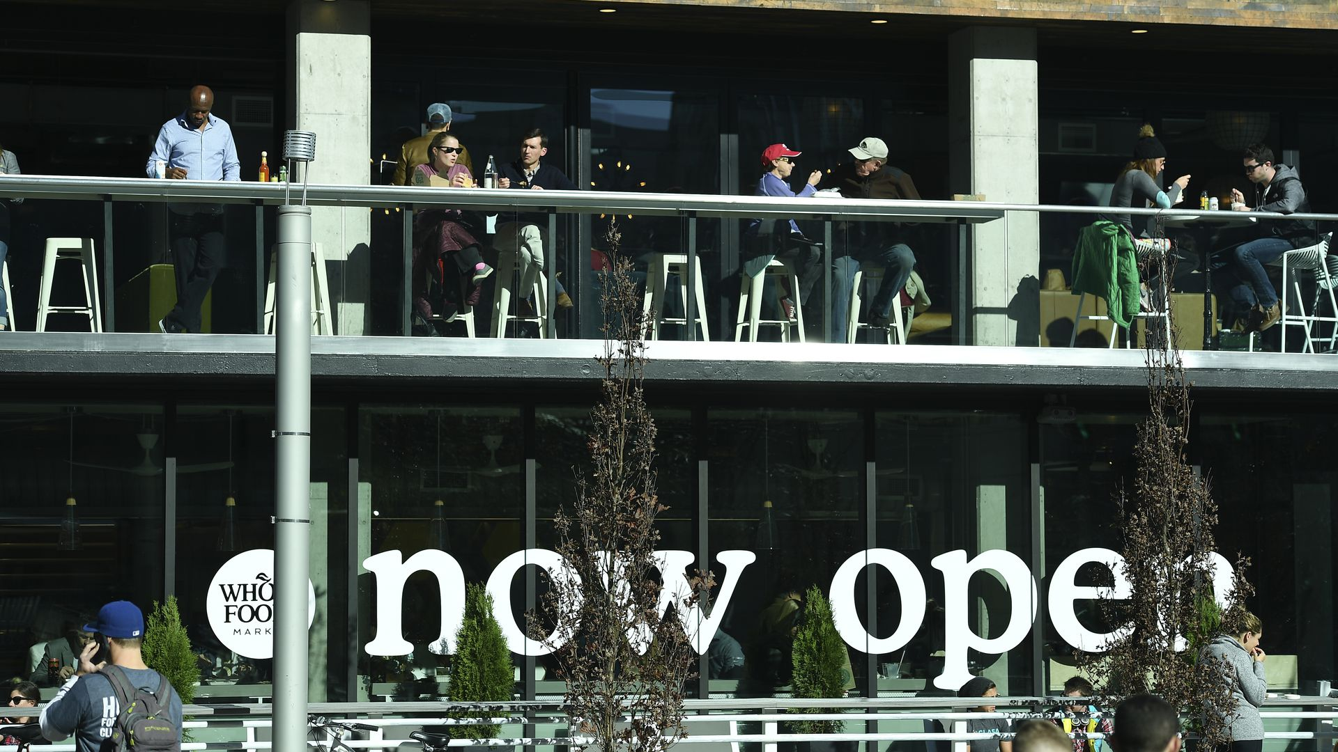 "Photo of a Whole Foods Market with the words ""now open"" written on the windows."