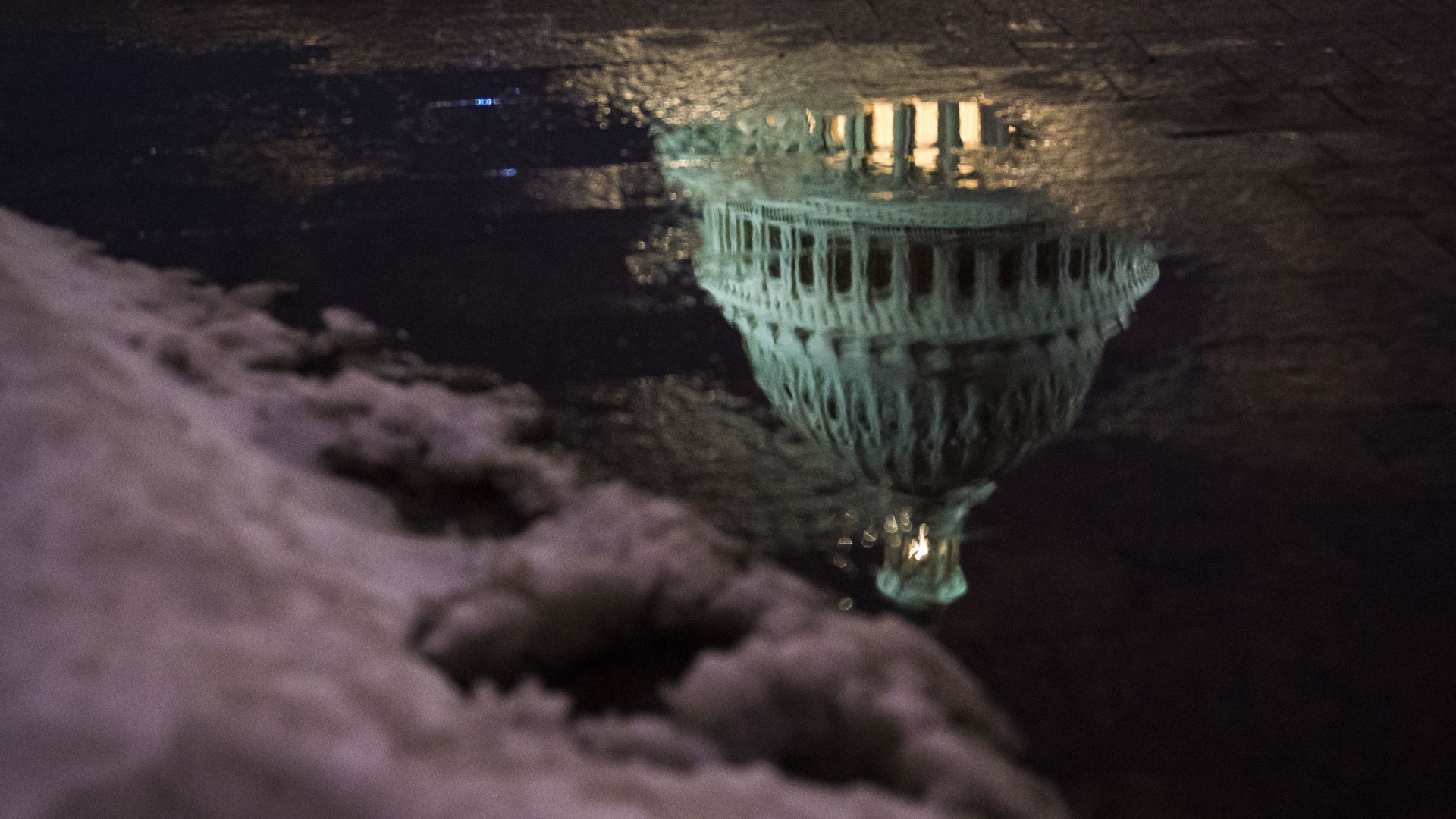 The Capitol dome is reflected in a puddle at dusk.