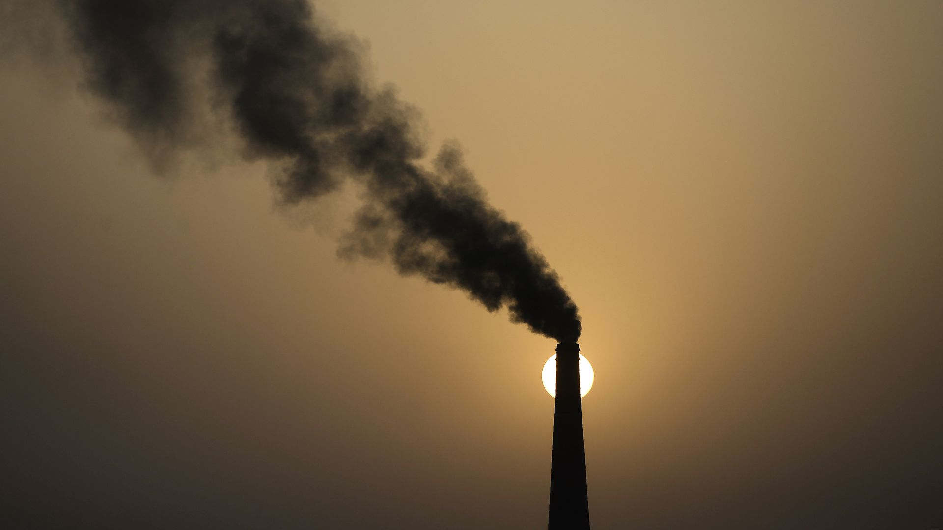 A chimney of a brick factory emits smoke during sunset in Jalandhar on May 31, 2018.