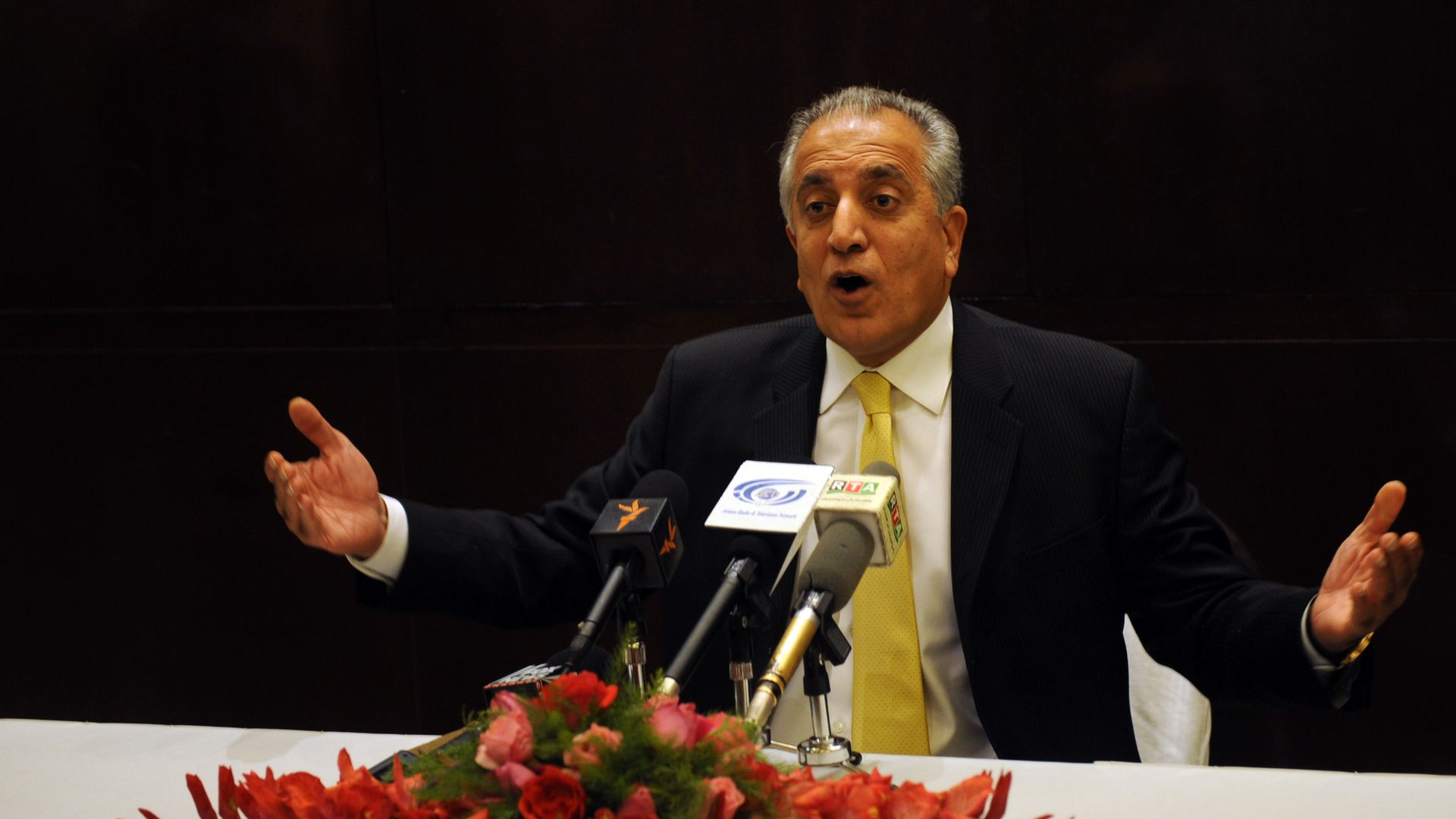 Zalmay Khalilzad speaks and gestures from a table with mics