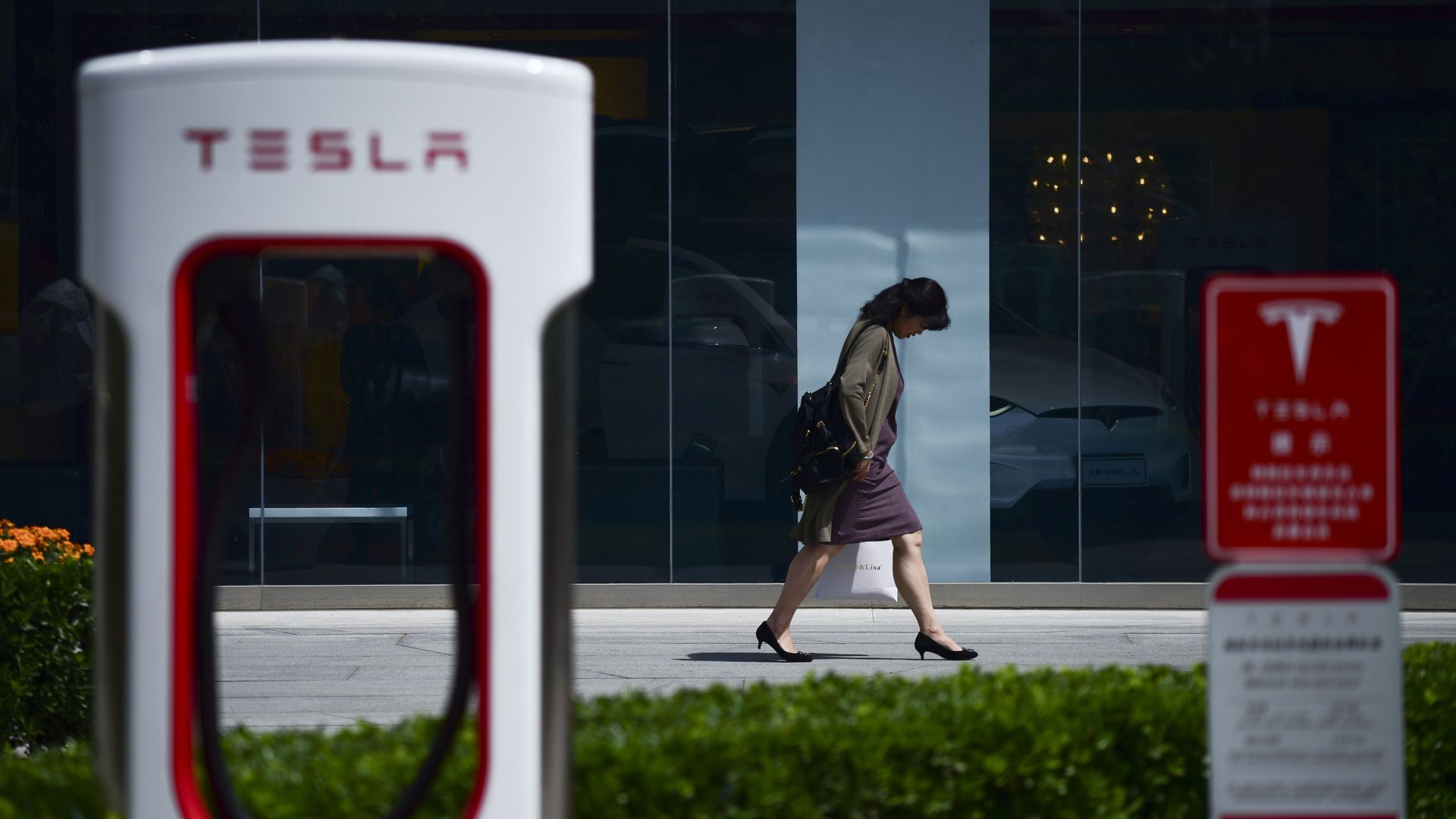 In this image, a woman walks past a Tesla charging port.