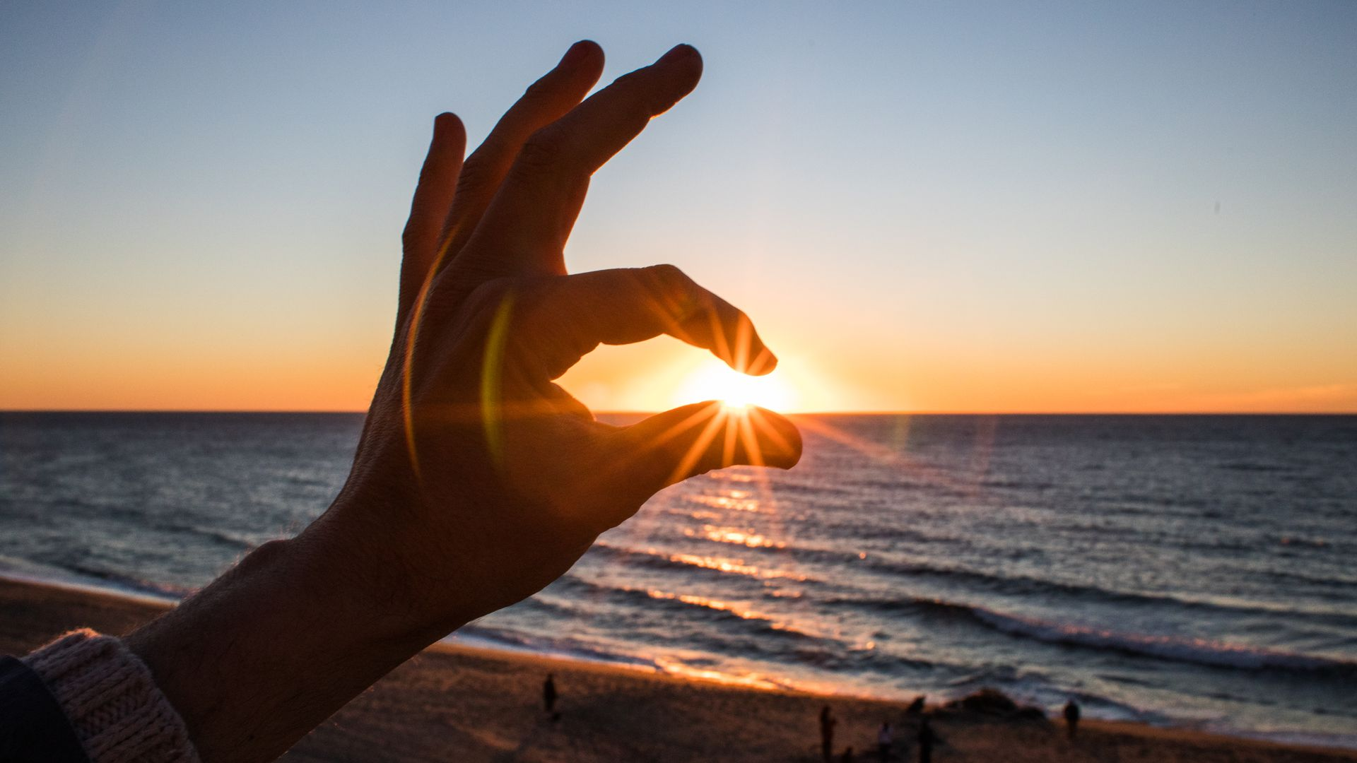 In this image, someone pretends to pinch the sun between two fingers as the sun sets at the beach.
