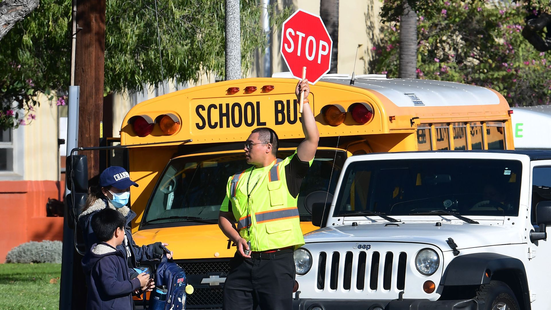 A man in a neon yellow vest holds up a stop sign in front of a school bus.