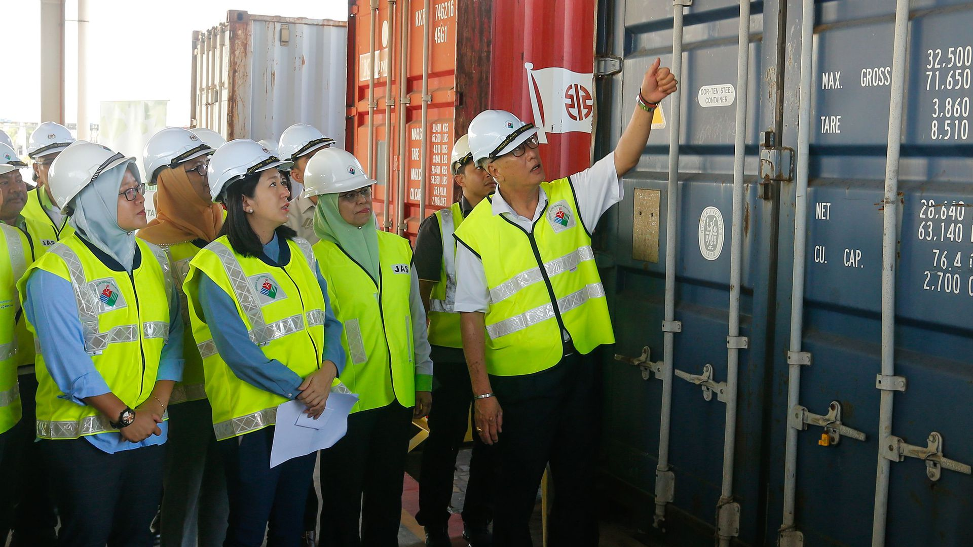 Malaysian Environment Minister Yeo Bee Yin (front 2nd L) and officials inspect a container containing plastic waste shipment on January 20, 2020 before sending back
