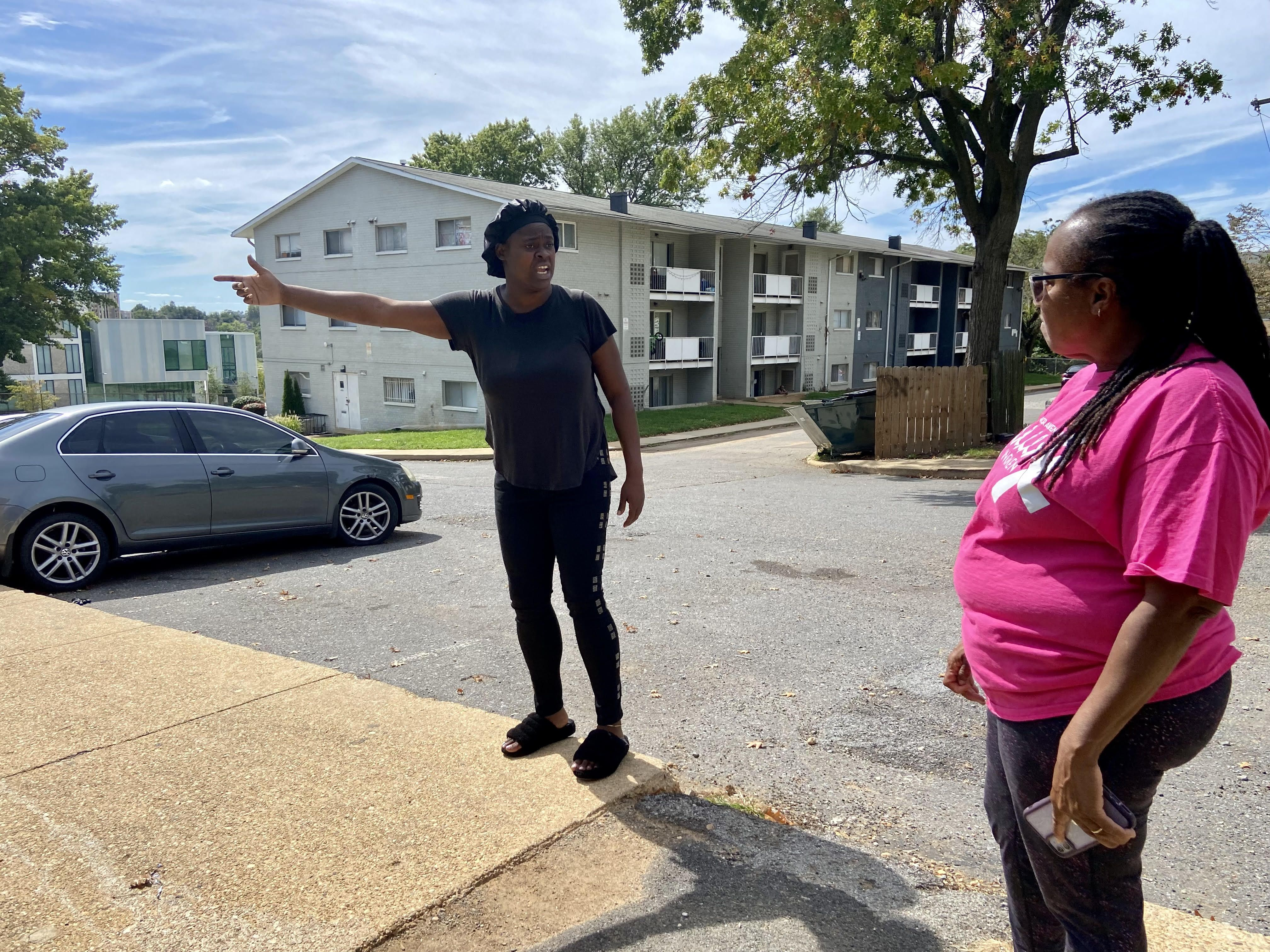 Two residents of Oak Hill Apartments discuss conditions at their complex in the courtyard.