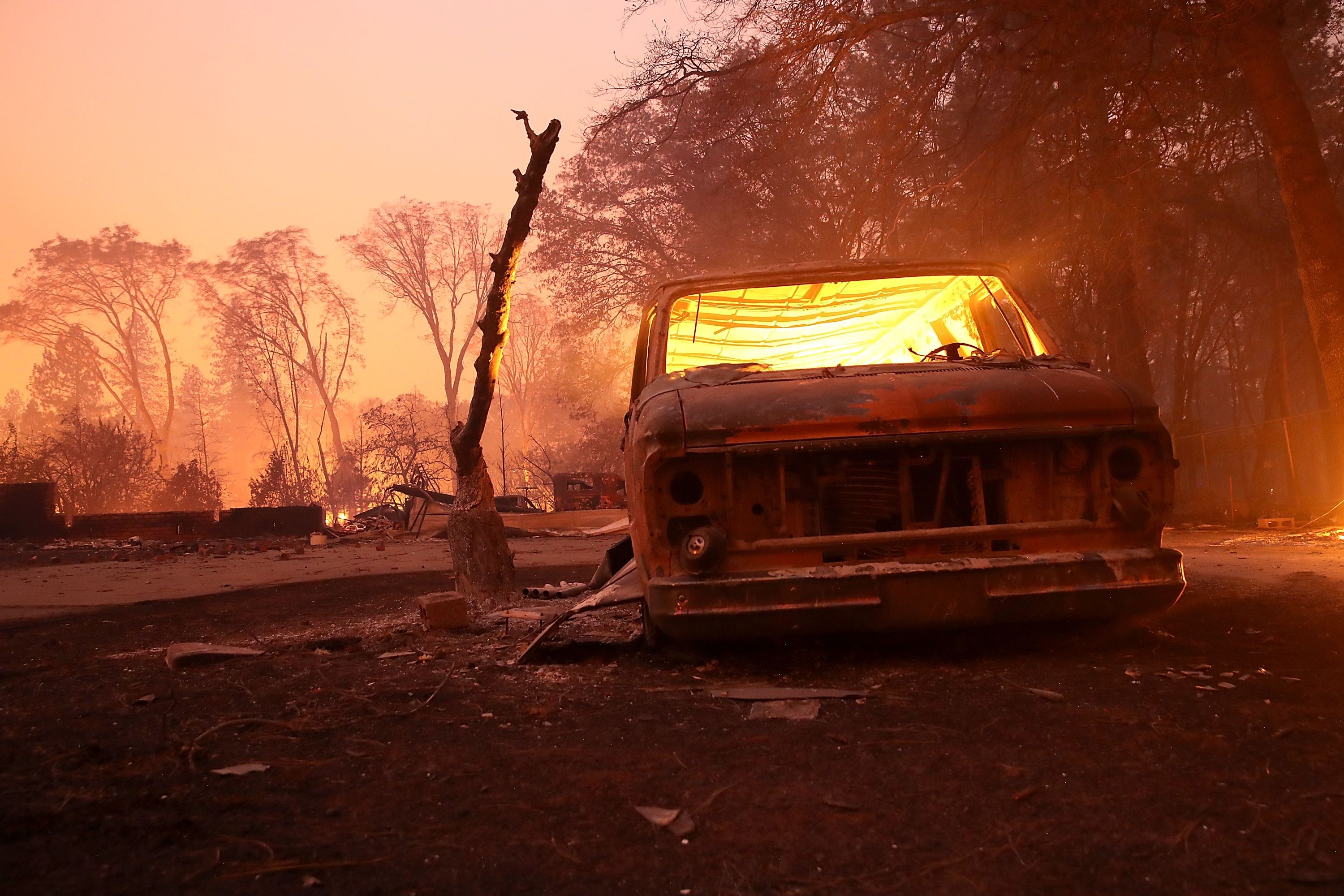 A burned out car on torched ground.