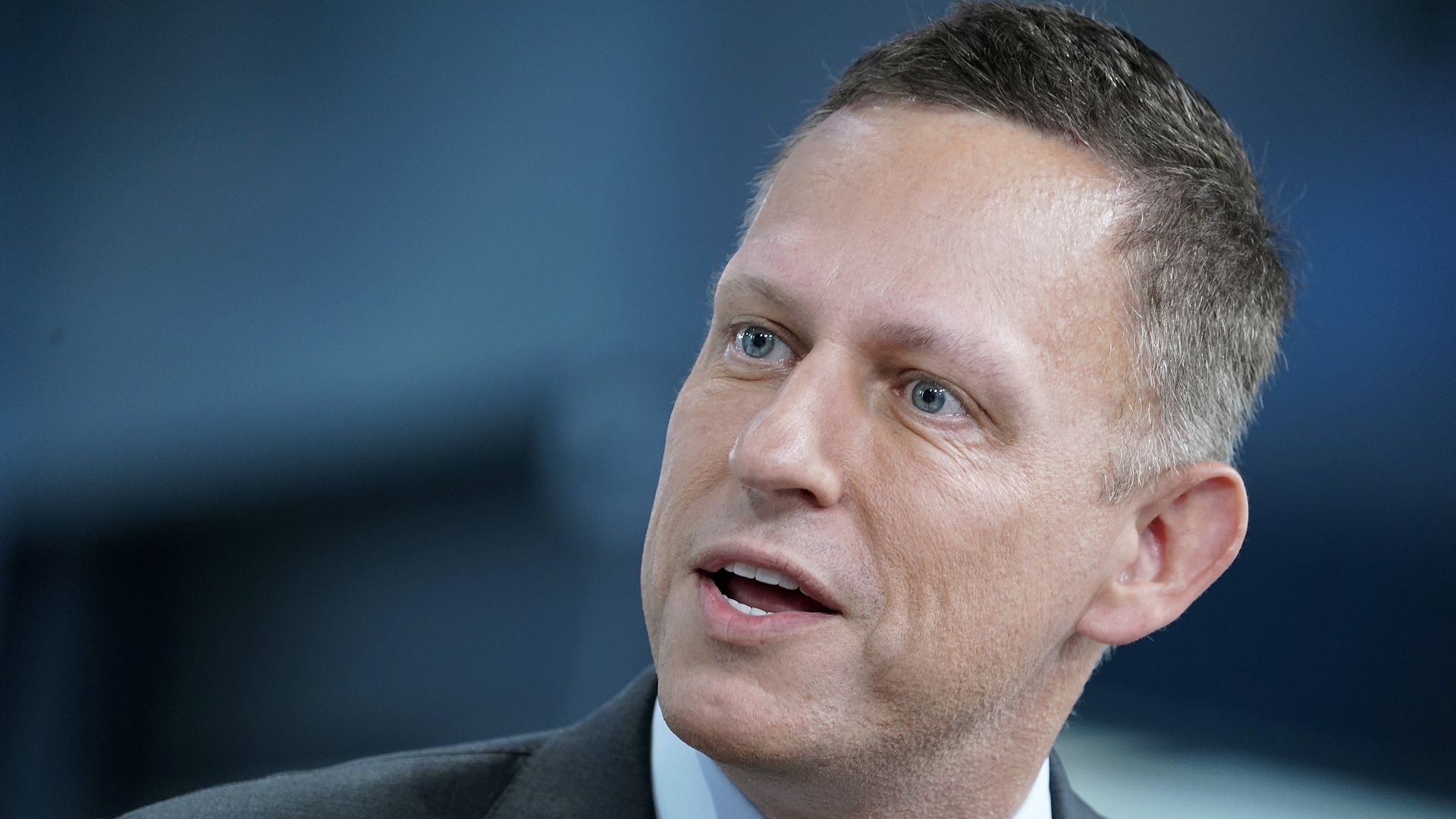 In this image, Peter Thiel wears a tie and suit and talks