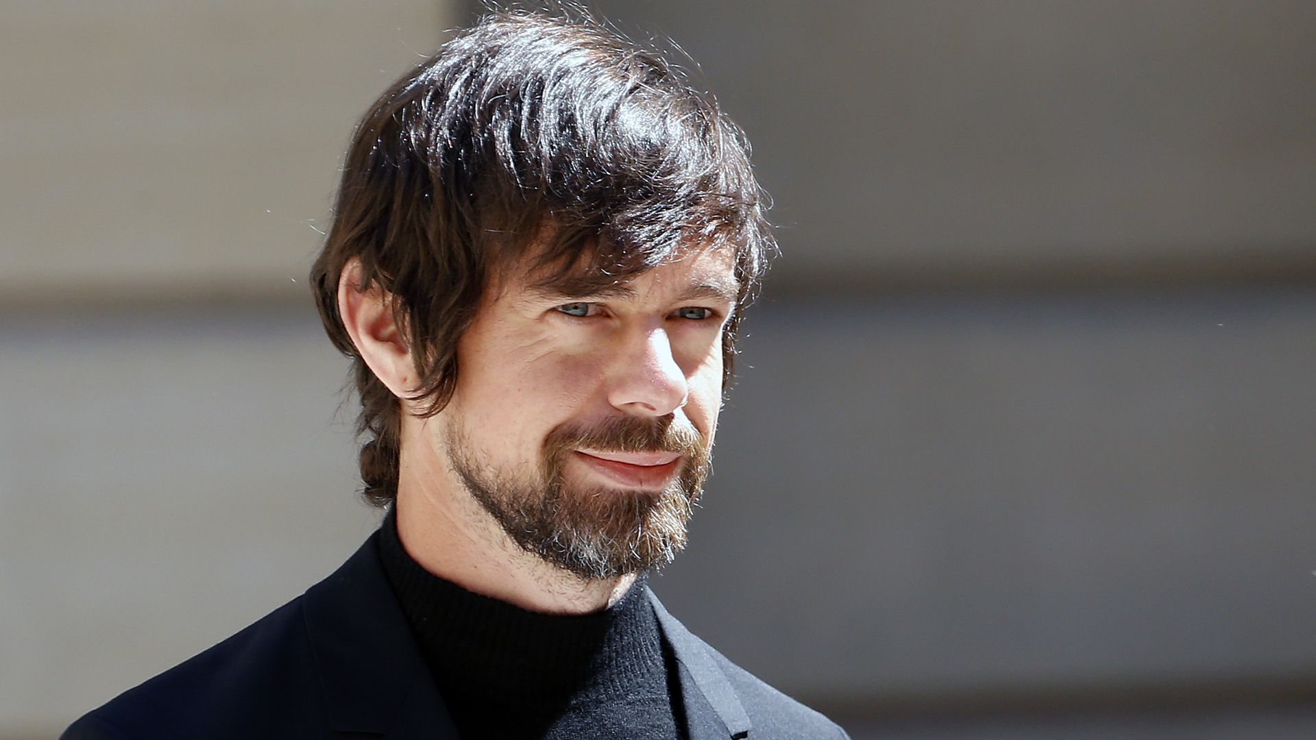 Photo of smiling Twitter CEO Jack Dorsey in black shirt and jacket