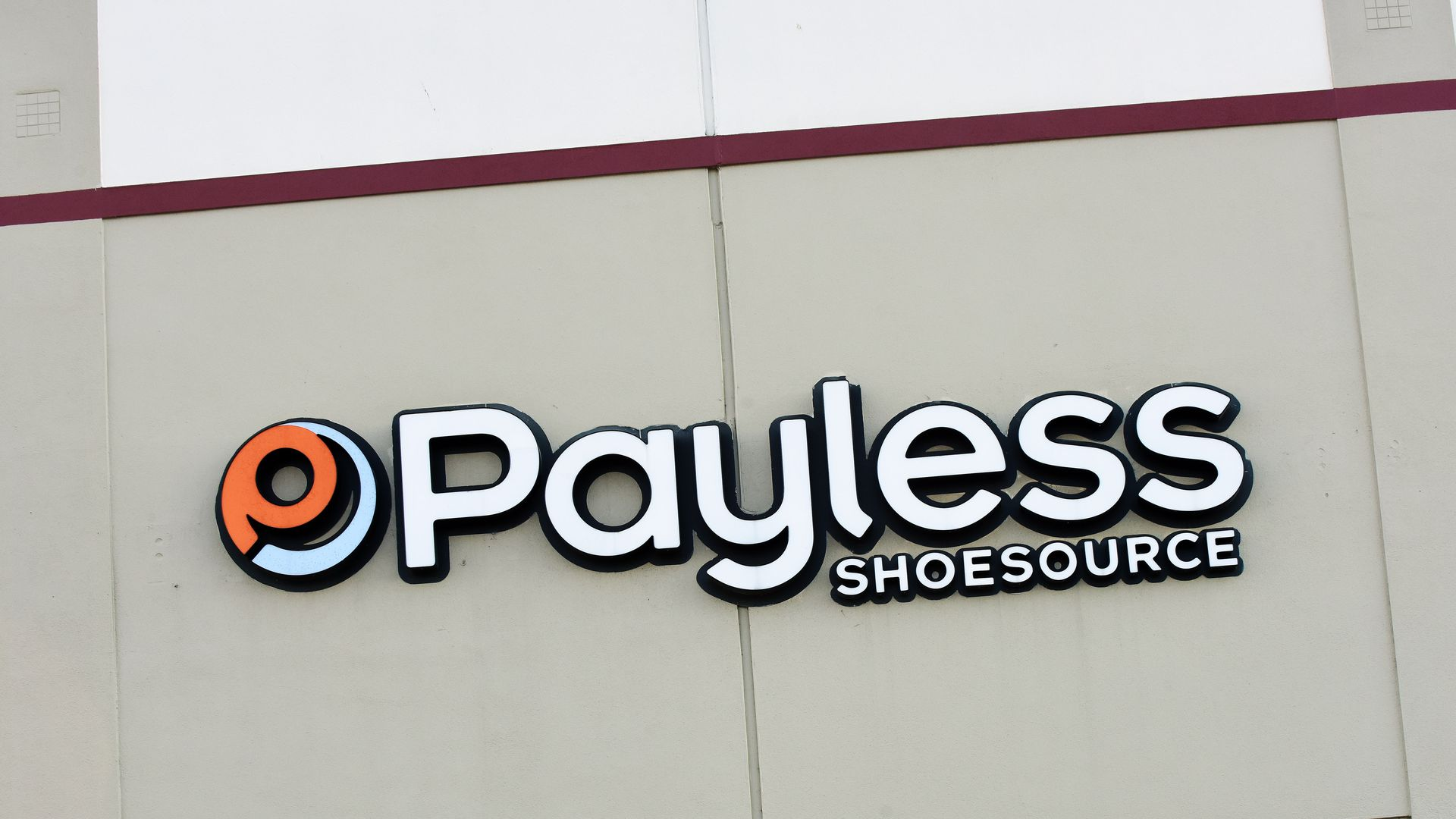In this image, the orange and white storefront sign for Payless ShoeSource is visible against a beige concrete wall.
