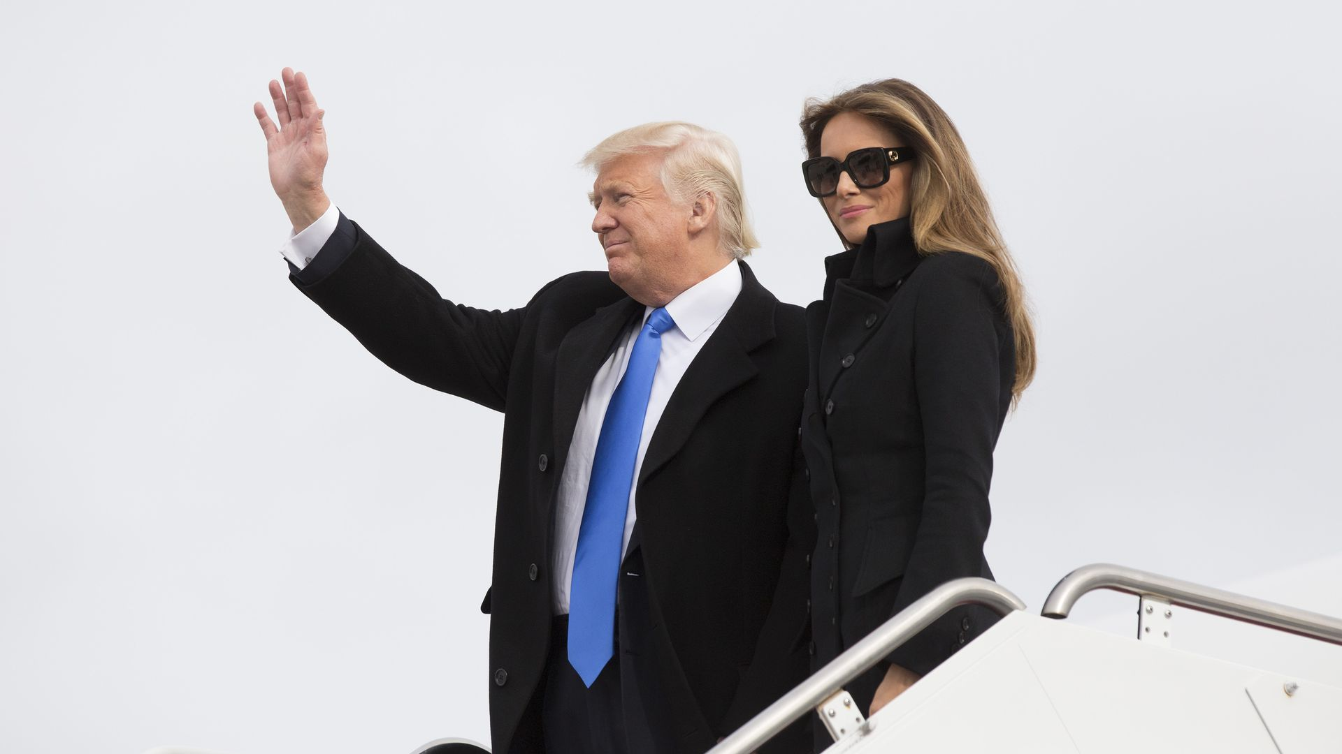 Donald Trump and Melania standing next to each other as the deplane from Air Force One. Trump is waving to a crowd. Melania is wearing all black and sunglasses and is smirking.