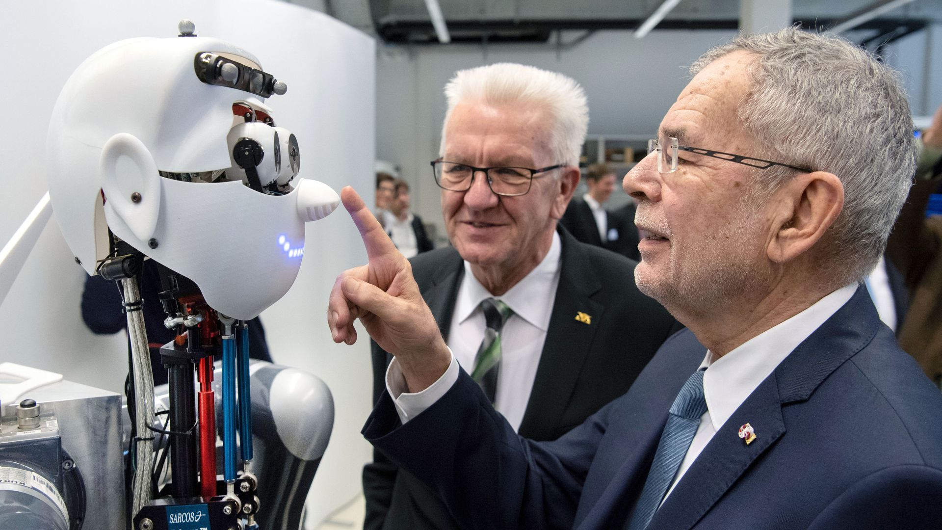 Photo of a man touching a robot's nose as another man looks on