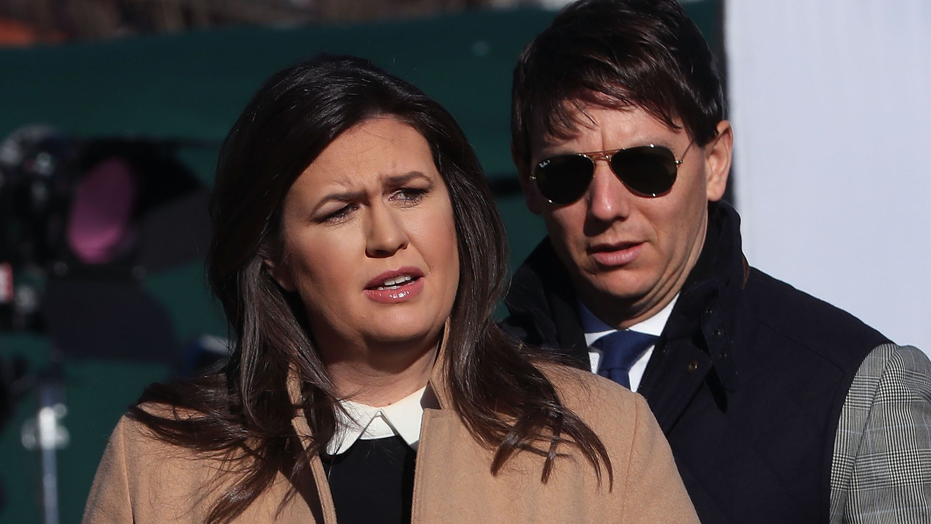 Sarah Sanders wears a quote while being interview outside the White House