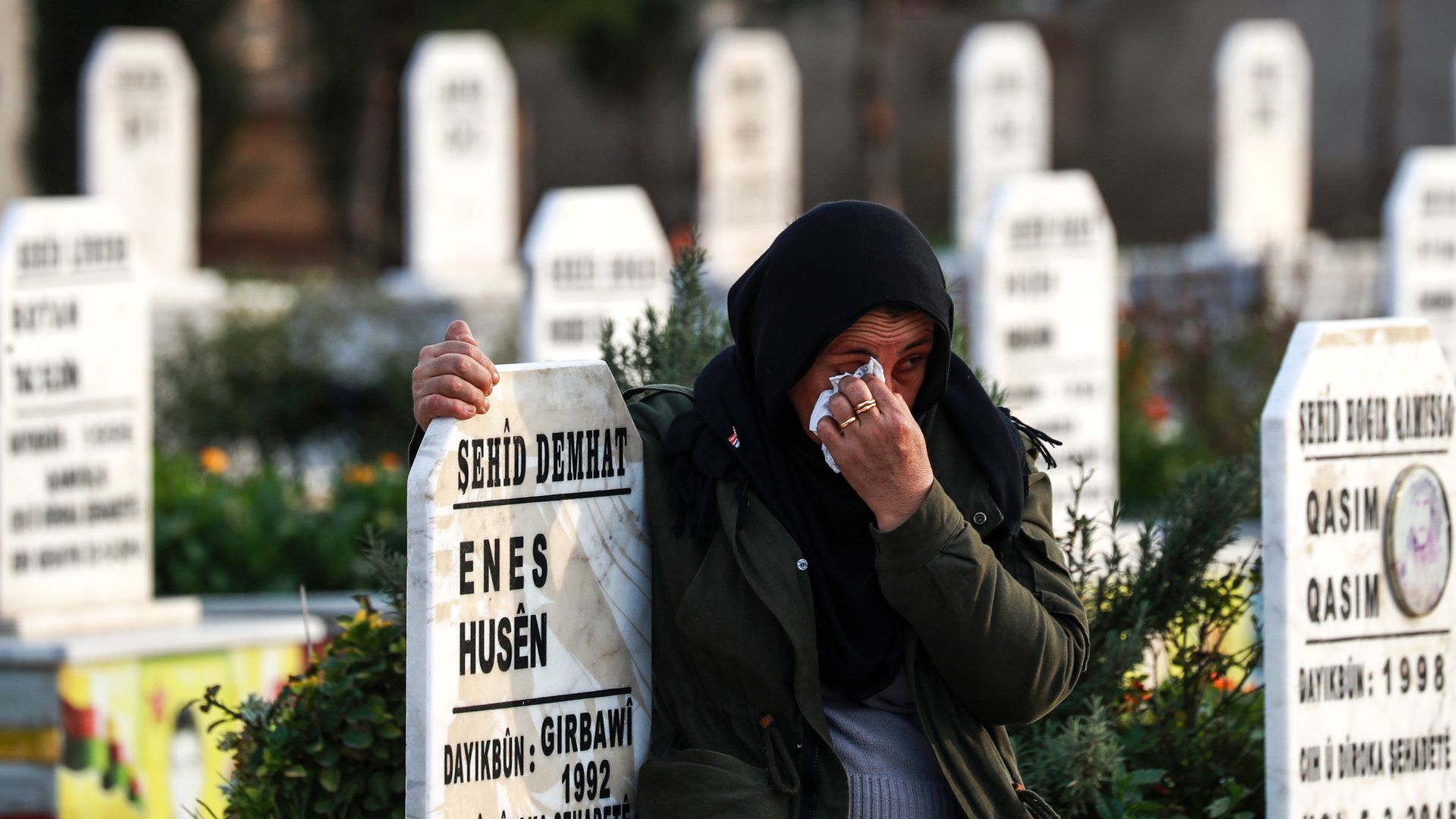 A Syrian Kurdish woman cries as she hugs the tombstone of a slain Syrian Democratic Forces fighter at a cemetery in the northeastern city of Qamishli
