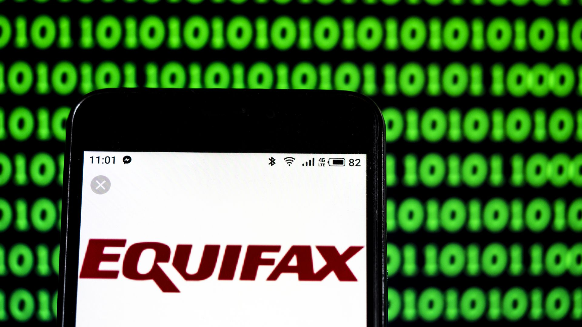 In this image, an iPhone is held close to the viewer against a green and black background of 1s and 0s. The phone screen is a white background with the logo 'Equifax' displayed in red.