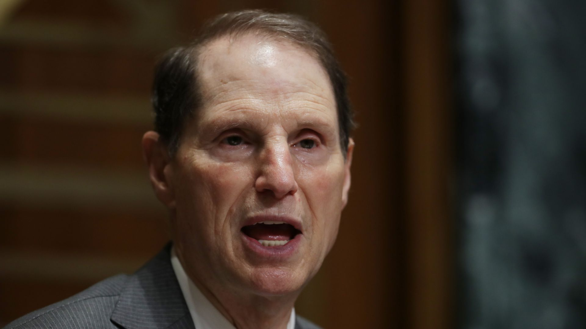 Sen. Ron Wyden speaks, wearing a suit