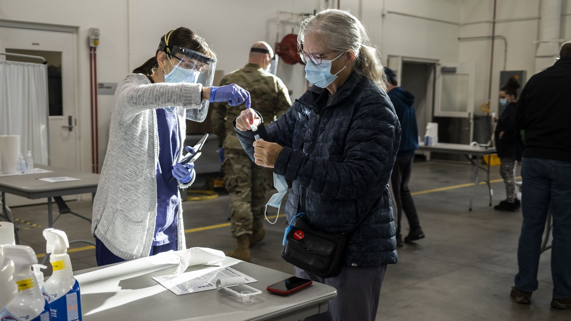 Photo of a masked person getting tested as a health care worker assists them