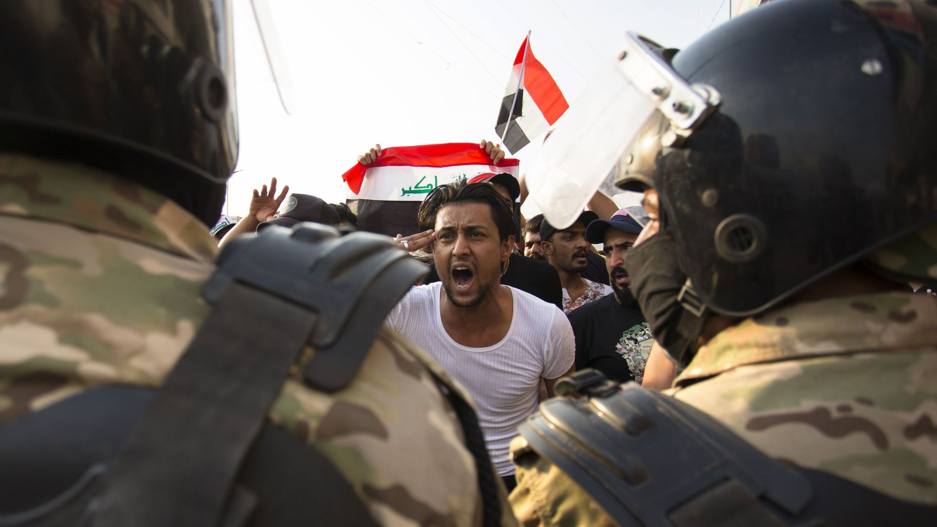 Iraqi protester gestures in front of armed forces
