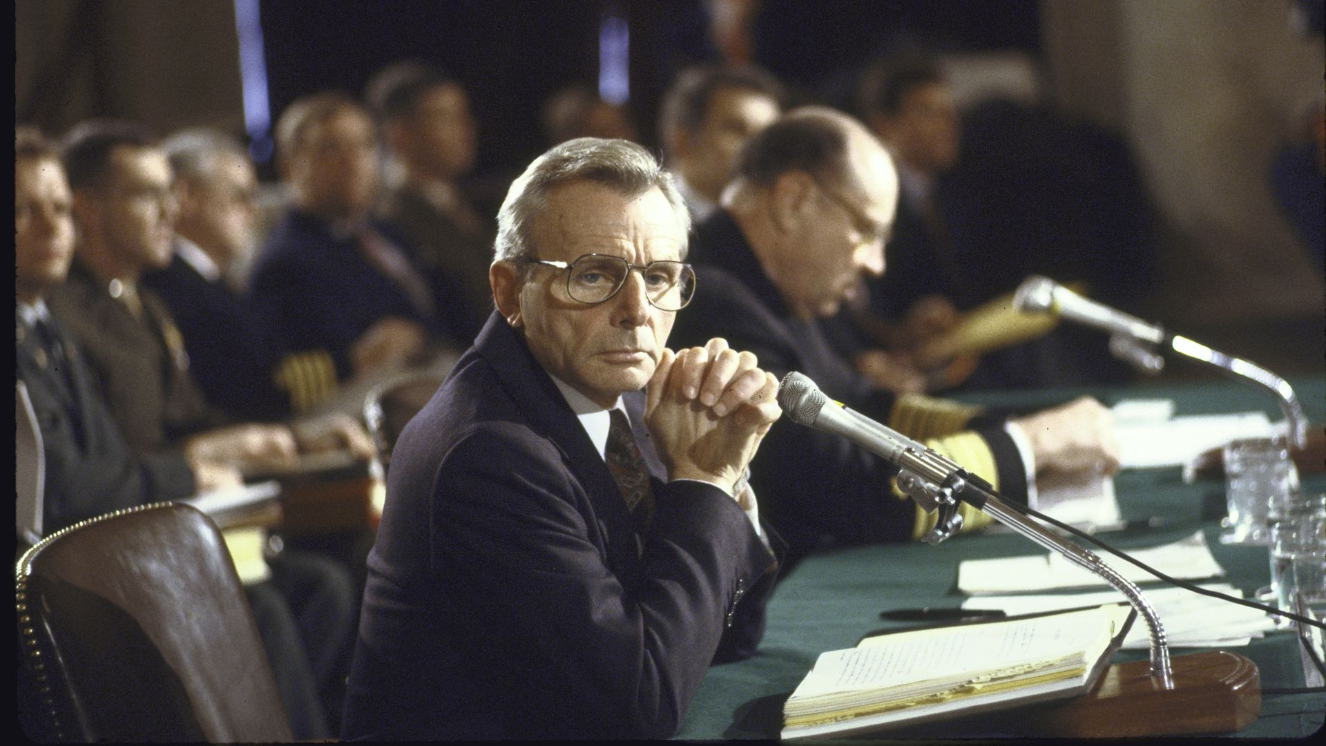 Frank Carlucci sits with hands steepled at a wooden table, looking towards the camera sideways.