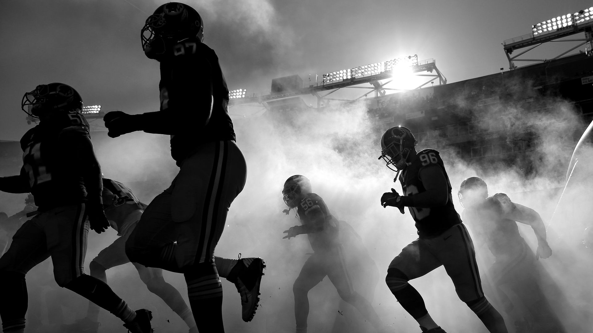 A black and white image: Washington football players run onto the field through a haze of fog.