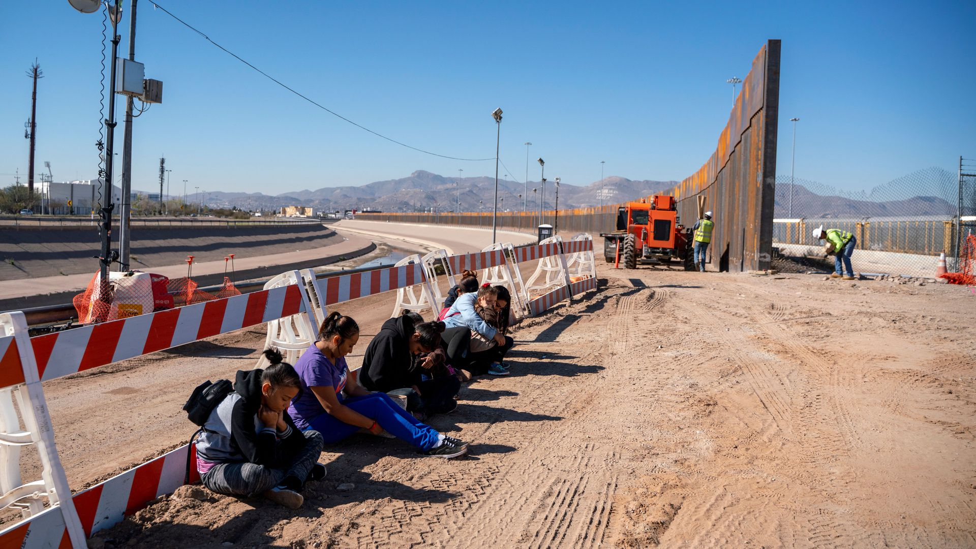 migrants wait for a transport to arrive after turning themselves into US Border Patrol by border fence under construction