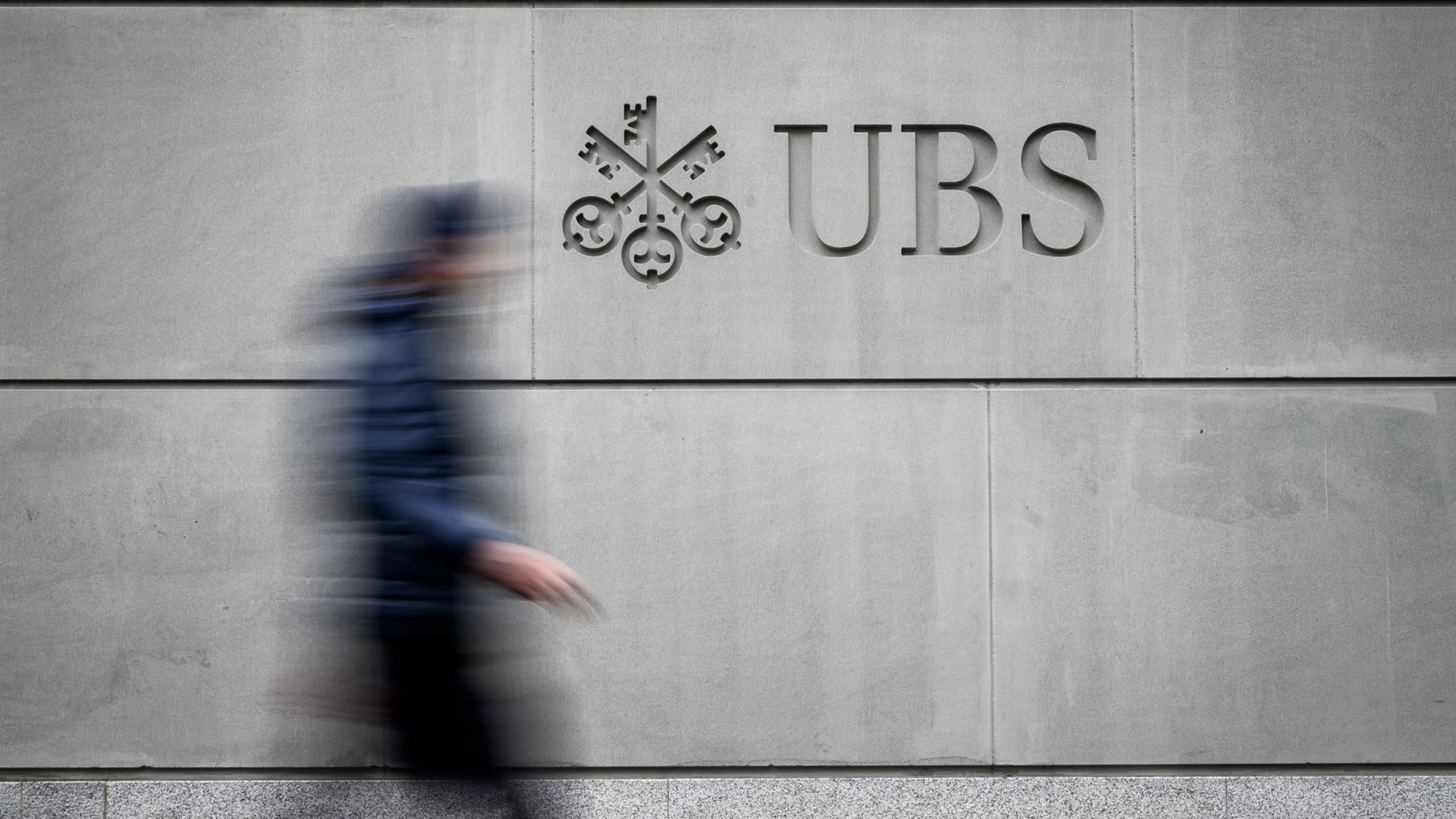 A pedestrian walks by the logo of Swiss banking giant UBS.