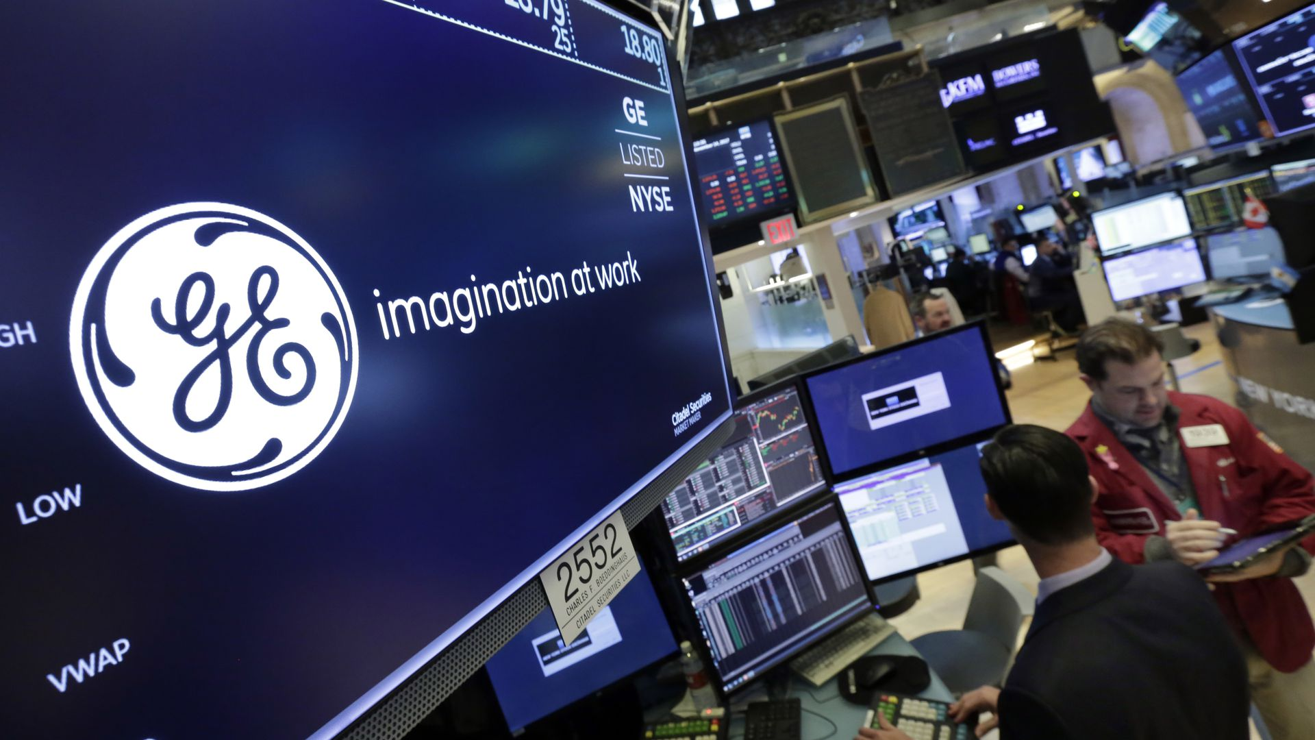 GE logo displayed on screens at a stock exchange, with traders in the background