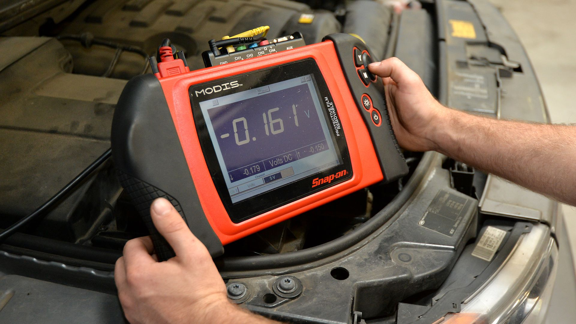 a mechanic holds a diagnostic device with display screen above open car hood and engine block