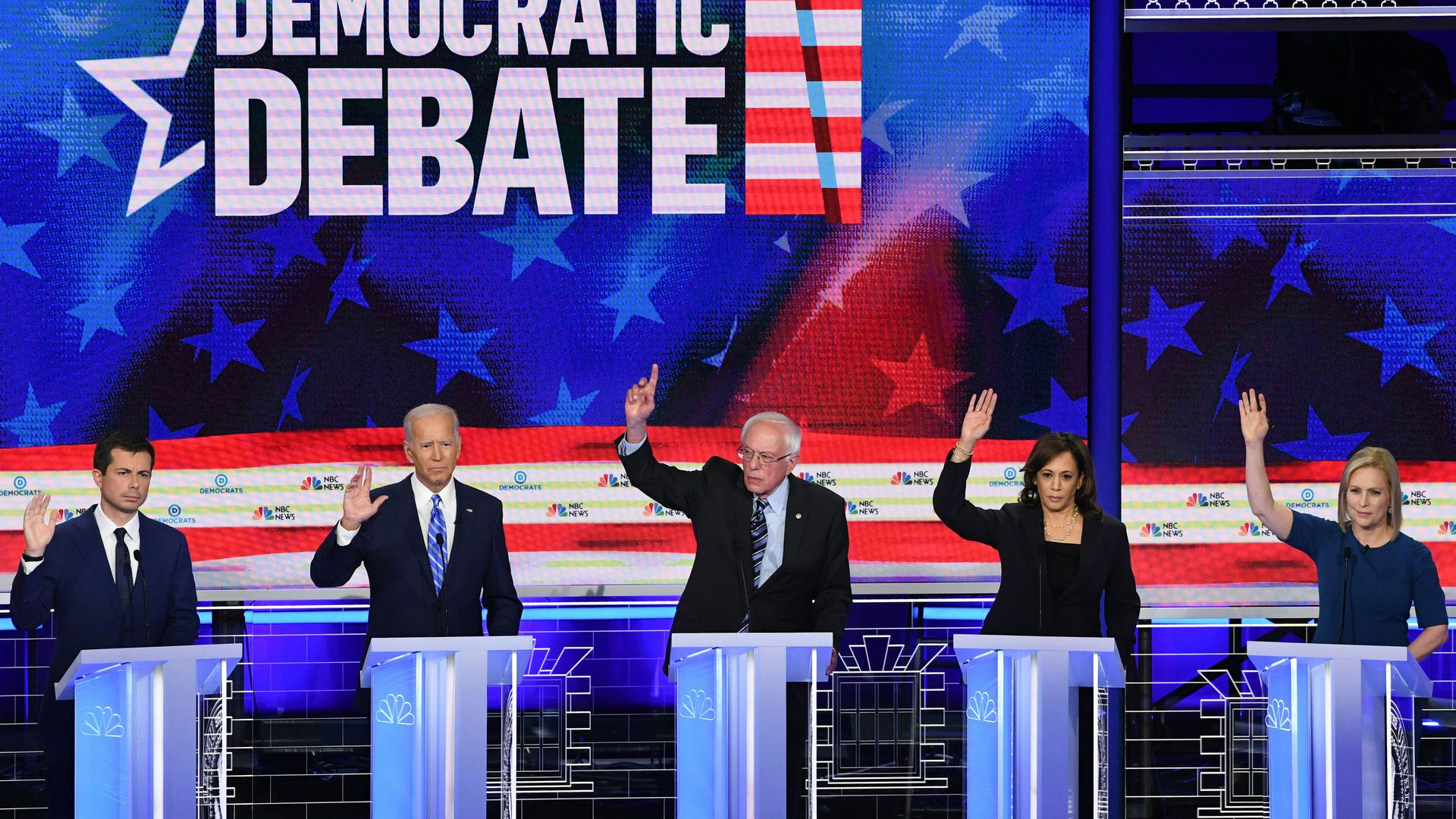 Democratic presidential candidates on the debate stage raise their hands
